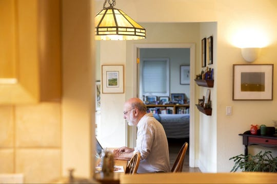 Retired University of California scientist Ed Vine works on his computer in his Berkeley home. The university is recruiting older homeowners to open their homes to students.