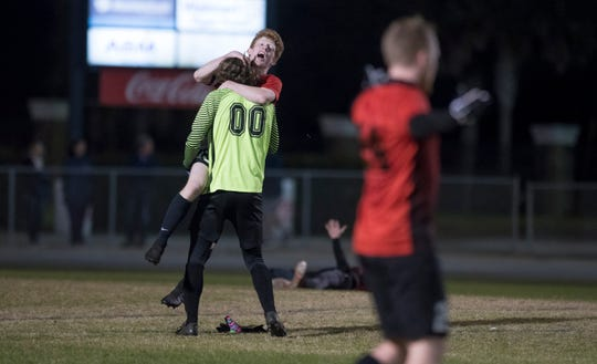 Jake Jenks (13) and goalie Mason Tampary (00) celebrate their victory in the District 1-3A boys soccer tournament final between West Florida and Gulf Breeze at Gulf Breeze High School on Friday, February 1, 2019.  The Jaguars defeated the Dolphin 3-1.