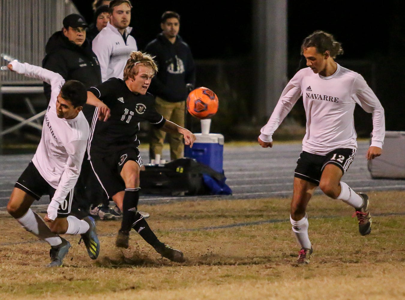 Navarre's Caleb Long (12) watches as teammate Joel Recinos (10) and Niceville's Brad Simmons (11) get tangled up while fighting for control of the ball in the District 1-4A championship game at Washington High School on Friday, February 1, 2019. For the second straight year, Niceville shut-out Navarre to win the championship. Last year, the score was 6-0 and this year it was 7-0.