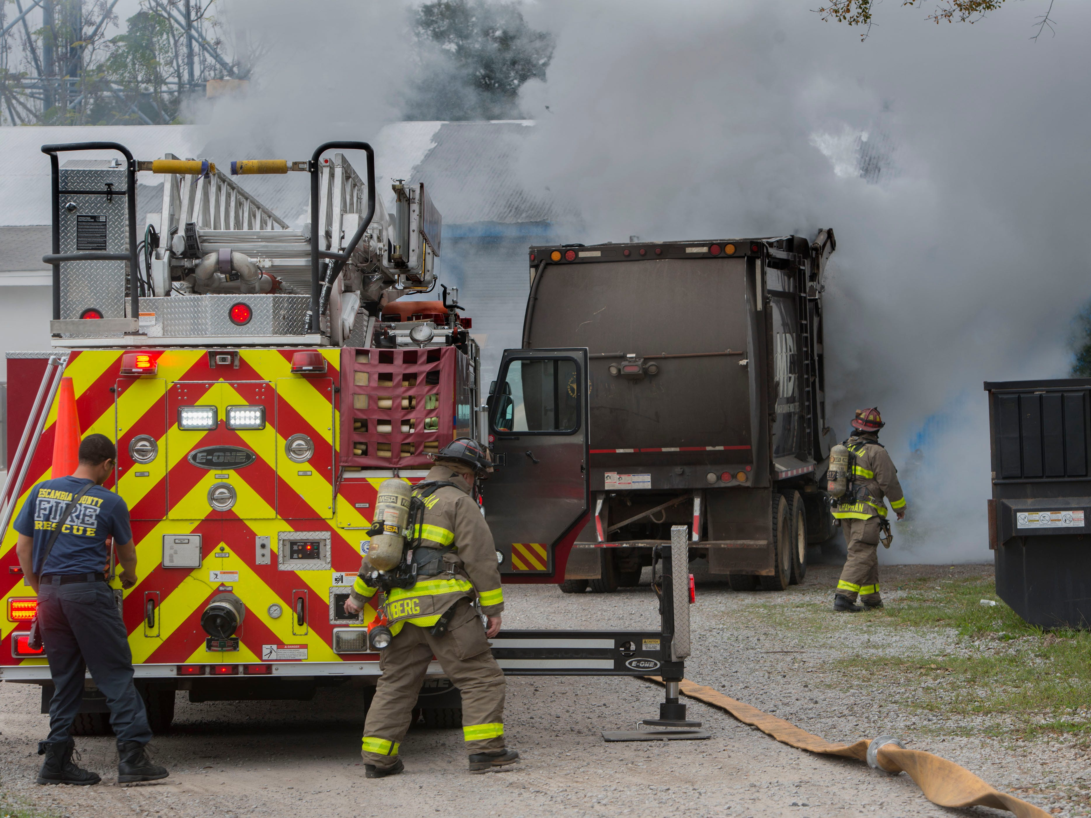 Firefighters battle a blaze in a garbage truck at Mark Dunning Industries Inc. Saturday, February 2, 2019.