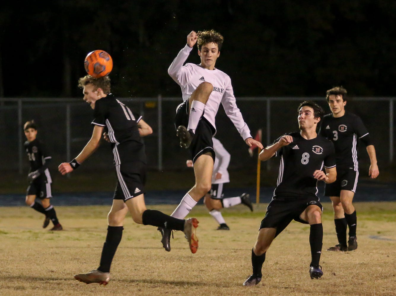 Niceville's Logan Harrelson, left, winces after getting clipped by the foot of Navarre's Jack Patching, jumping, in the District 1-4A championship game at Washington High School on Friday, February 1, 2019. For the second straight year, Niceville shut-out Navarre to win the championship. Last year, the score was 6-0 and this year it was 7-0.
