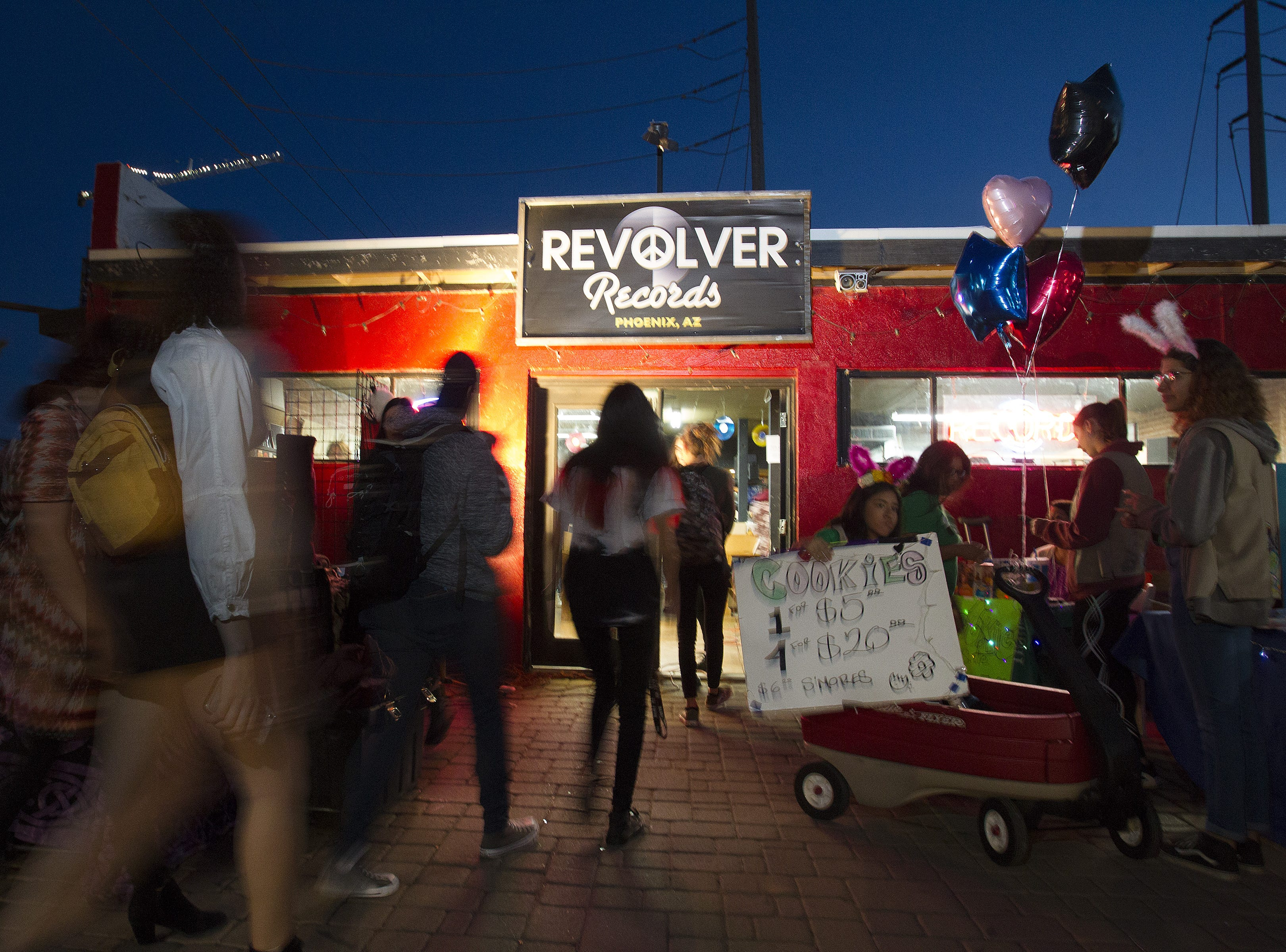 Music lovers make their way into Revolver Records as Girl Scouts sell cookies during First Friday in downtown Phoenix, Feb. 1, 2019. Revolver Records has all merchandise at 50 percent off and will be closing its doors Feb. 10.