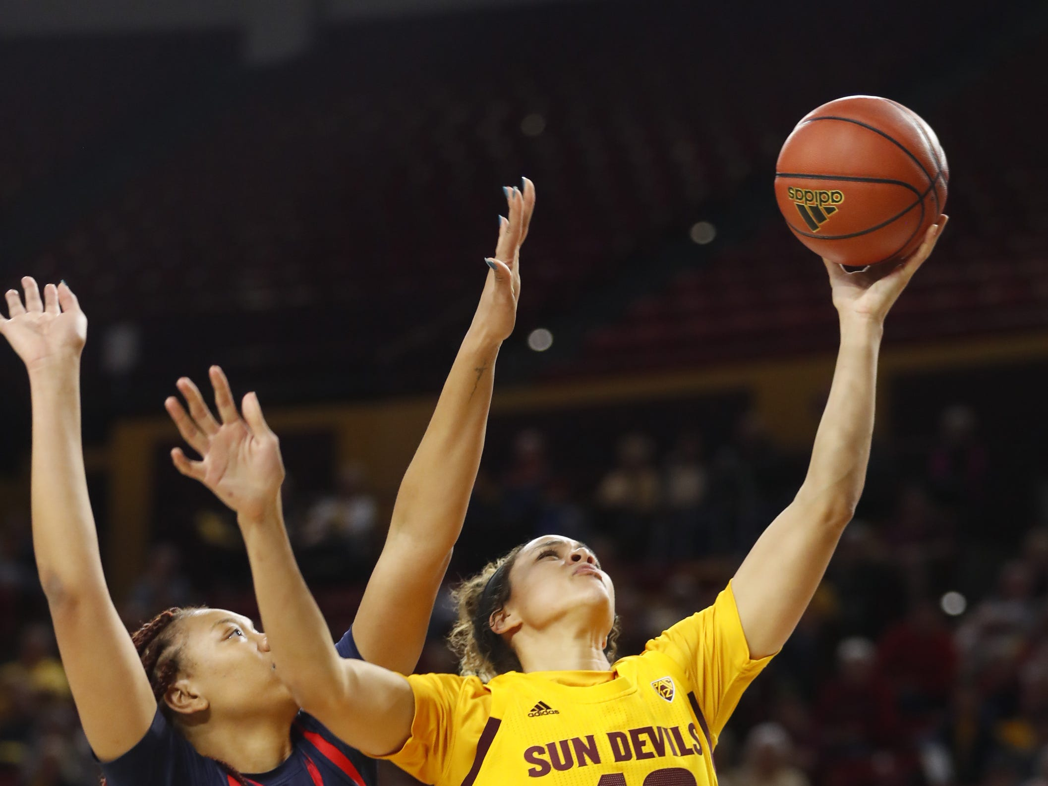 ASU's Kianna Ibis (42) makes a layup against Arizona's Semaj Smith (34) during the second half at Wells Fargo Arena in Tempe, Ariz. on February 1, 2019.
