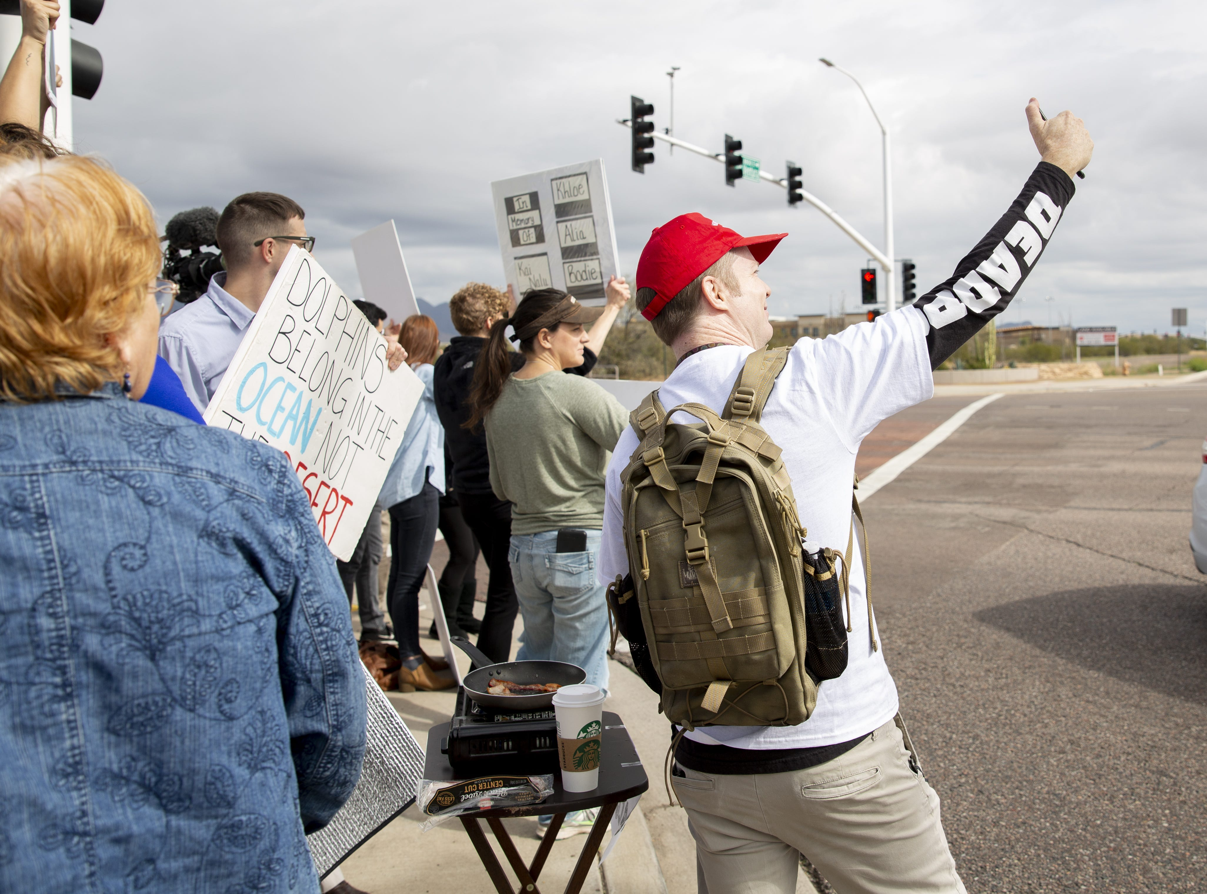 A counter-protester, right, at the Dolphinaris protest takes a selfie at the intersection of E. Via de Ventura and N. Pima Road in Scottsdale on Feb. 2, 2019.