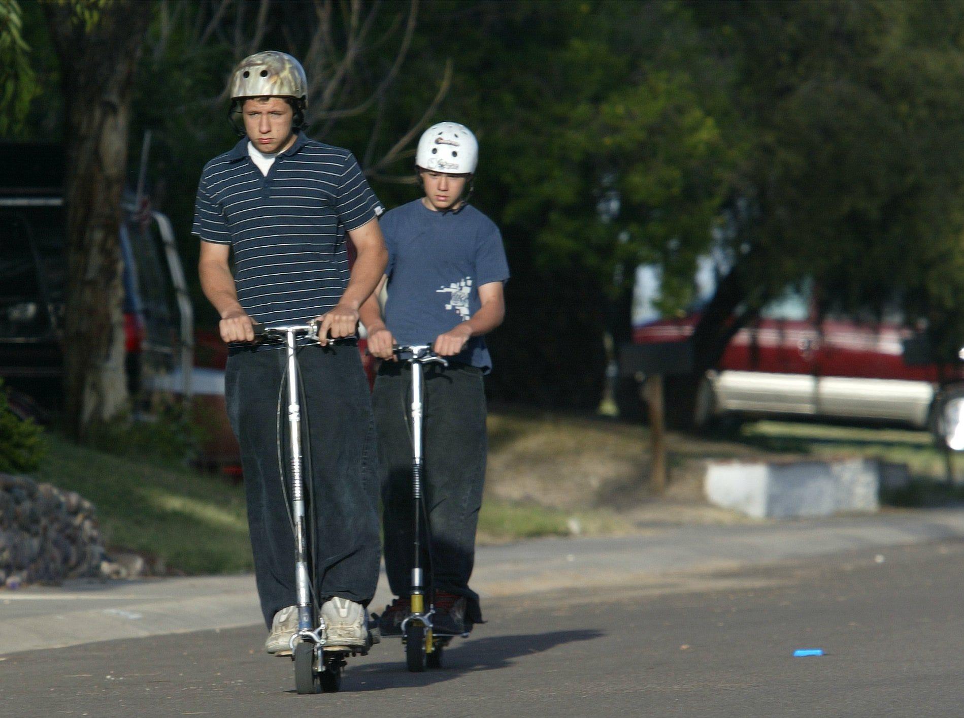 Scott White, then 15, right, and Tim Clark, then 17, ride their go-peds, or electric skateboards, on Buffalo Street in Chandler in this 2003 file photo.