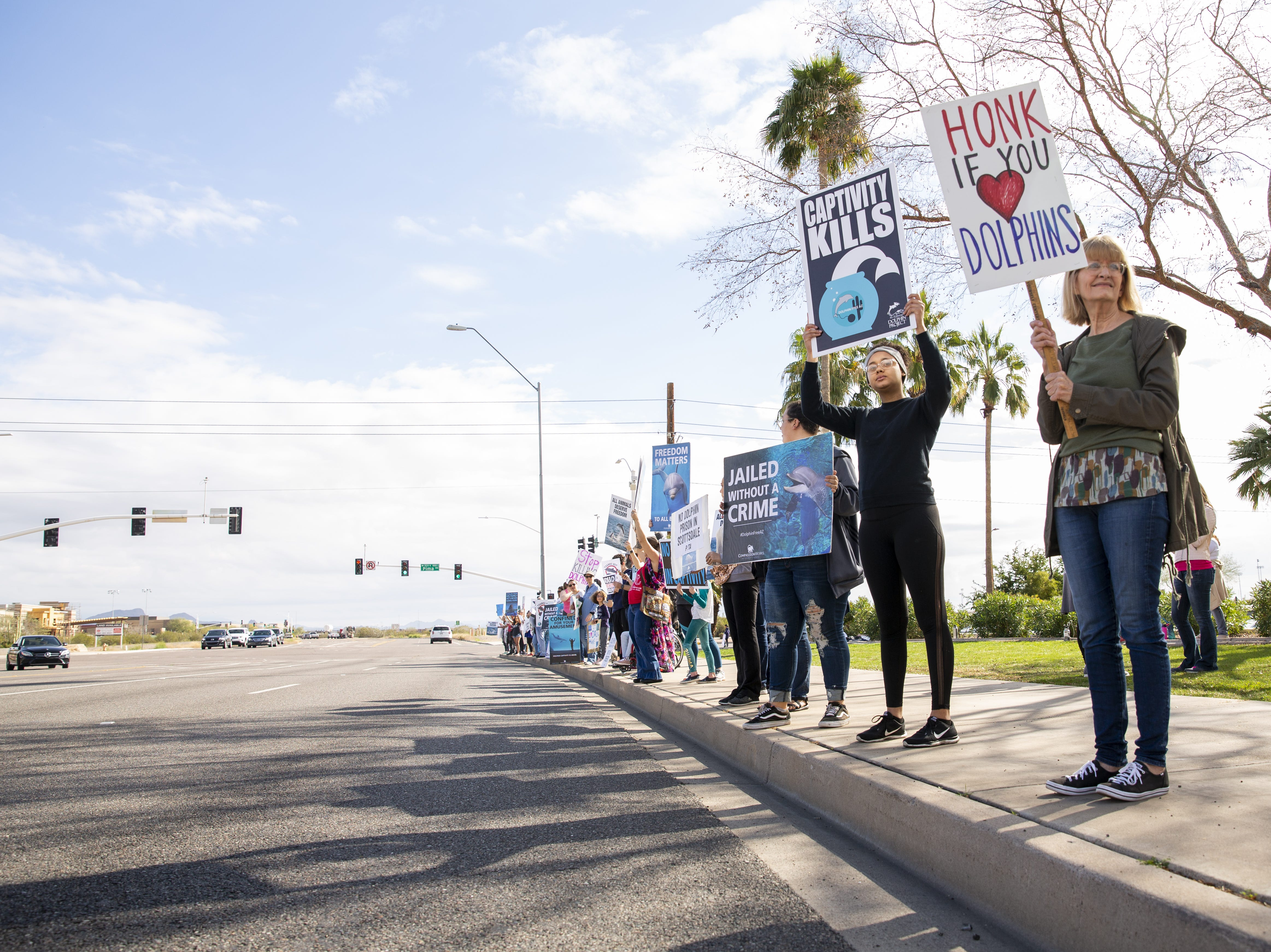 From right, Jeanne Carney and Chyna Douglas hold signs in protest of Dolphinaris at the intersection of E. Via de Ventura and N. Pima Road in Scottsdale on Feb. 2, 2019. The protest was prompted by four dolphin deaths in less than two years.