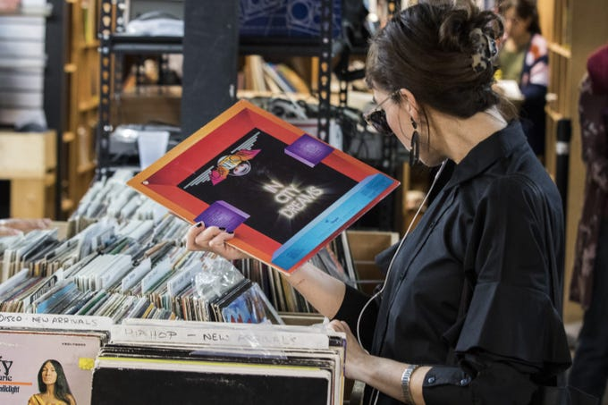 During First Friday, a music lover reads the jacket cover of a Robin Trower's album as she visits Revolver Records in downtown Phoenix, Feb. 1, 2019. Revolver Records has all merchandise at 50 percent off and will be closing its doors Feb. 10.