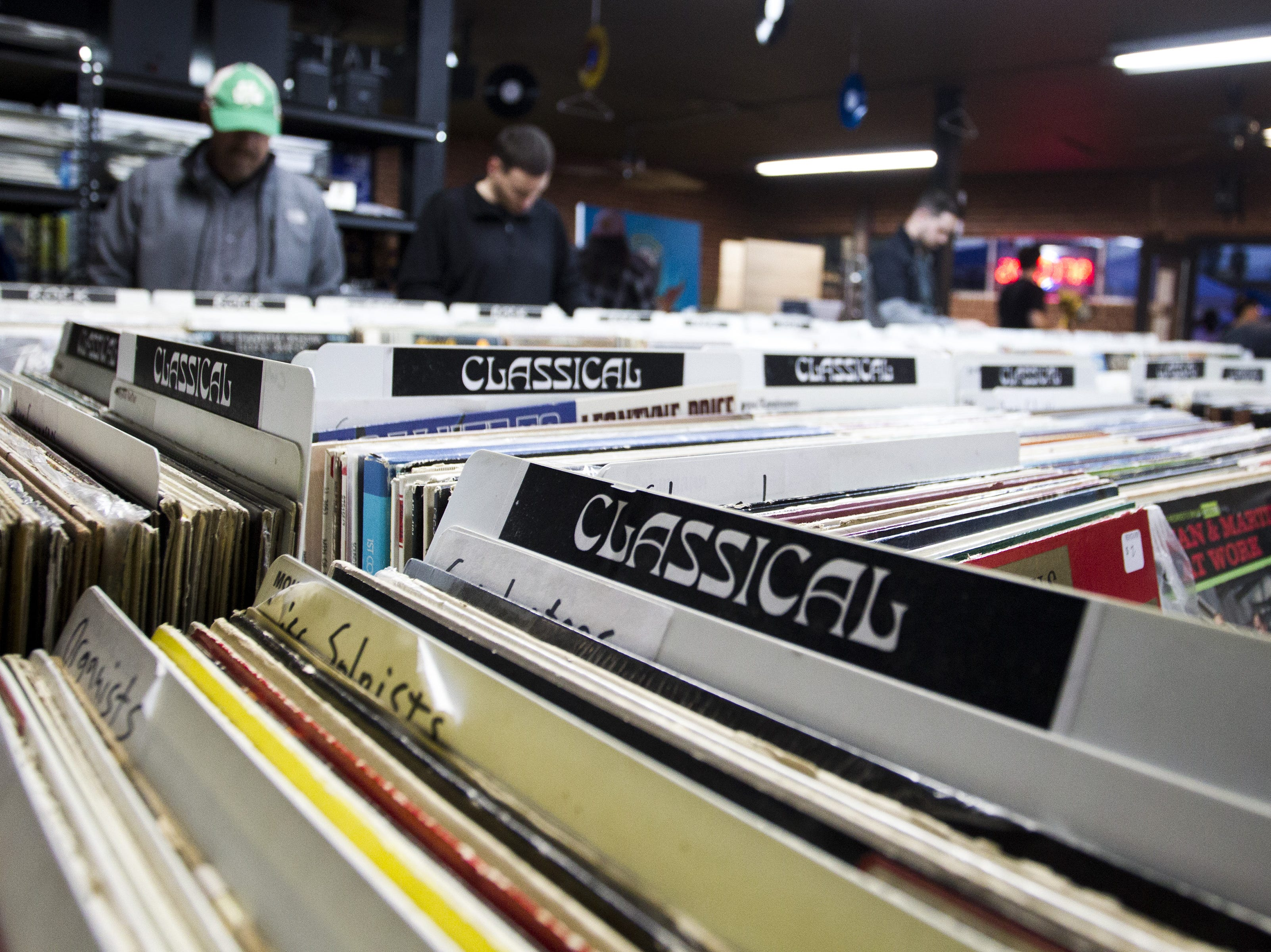 Music lovers sort through albums at Revolver Records in downtown Phoenix on First Friday. Revolver Records has all merchandise at 50 percent off and will be closing its doors Feb. 10.