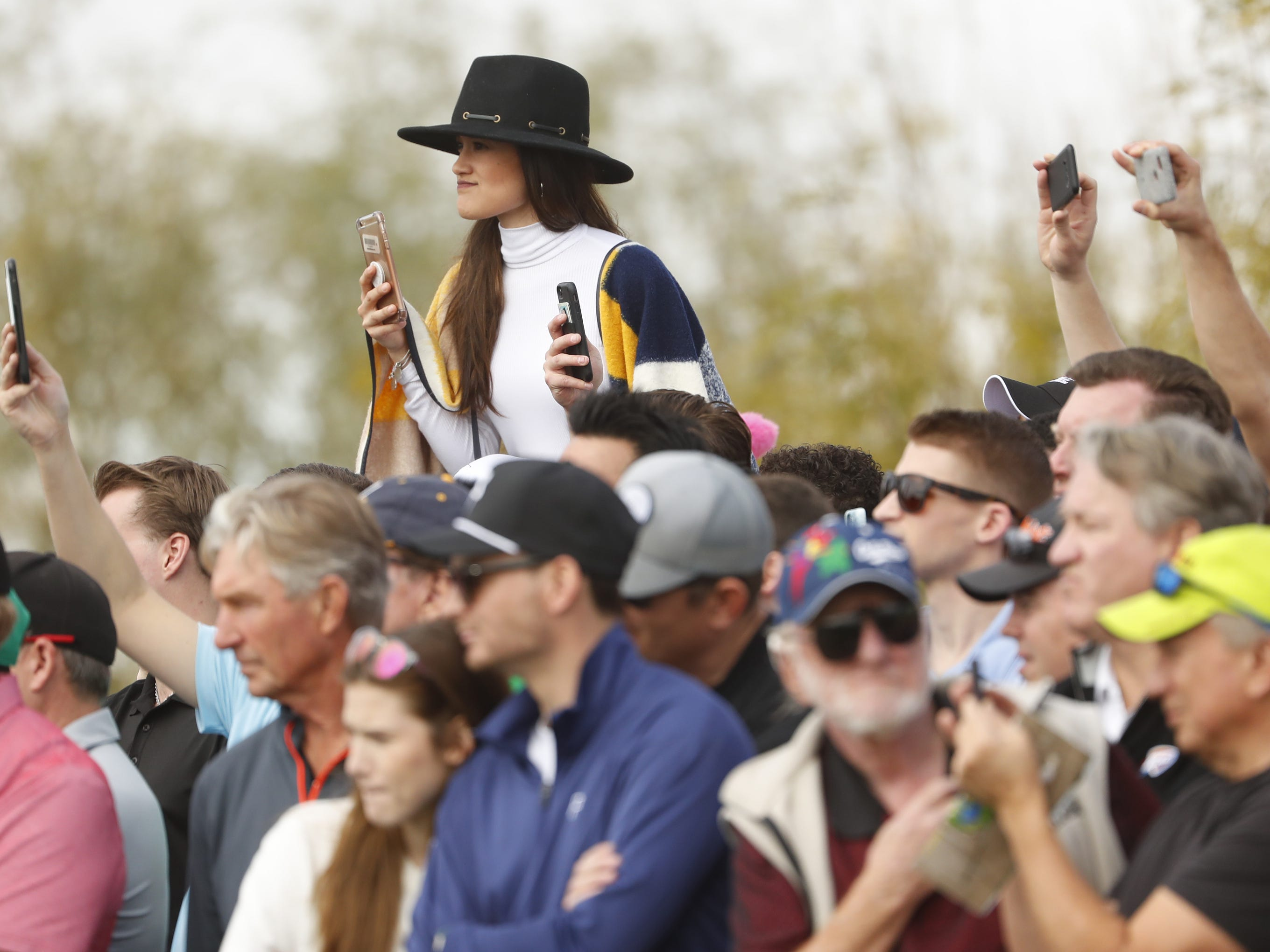 A woman looks at golfers teeing off on the 8th hole from atop her friends shoulders during the third round of the Waste Management Phoenix Open at TPC Scottsdale in Scottsdale, Ariz. on February 2, 2019.