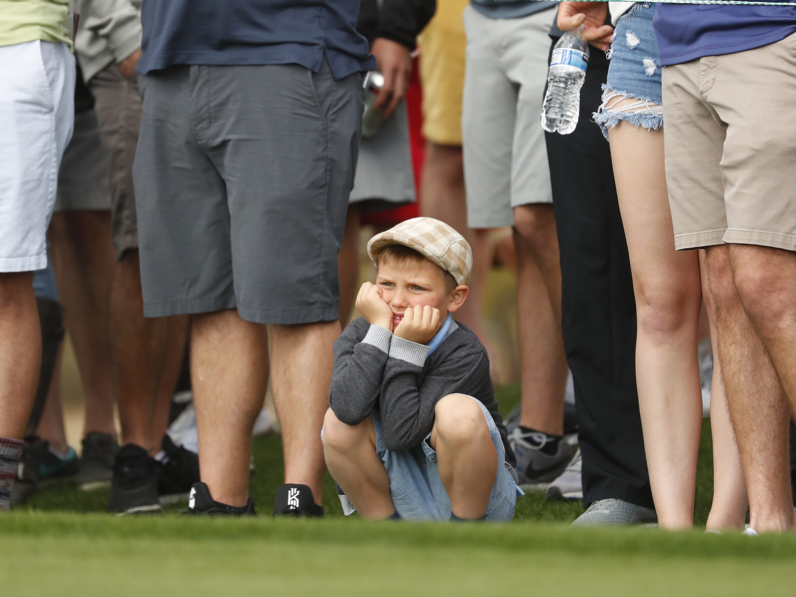 A child watches golfers tee off on the 8th hole during the third round of the Waste Management Phoenix Open at TPC Scottsdale in Scottsdale, Ariz. on February 2, 2019.