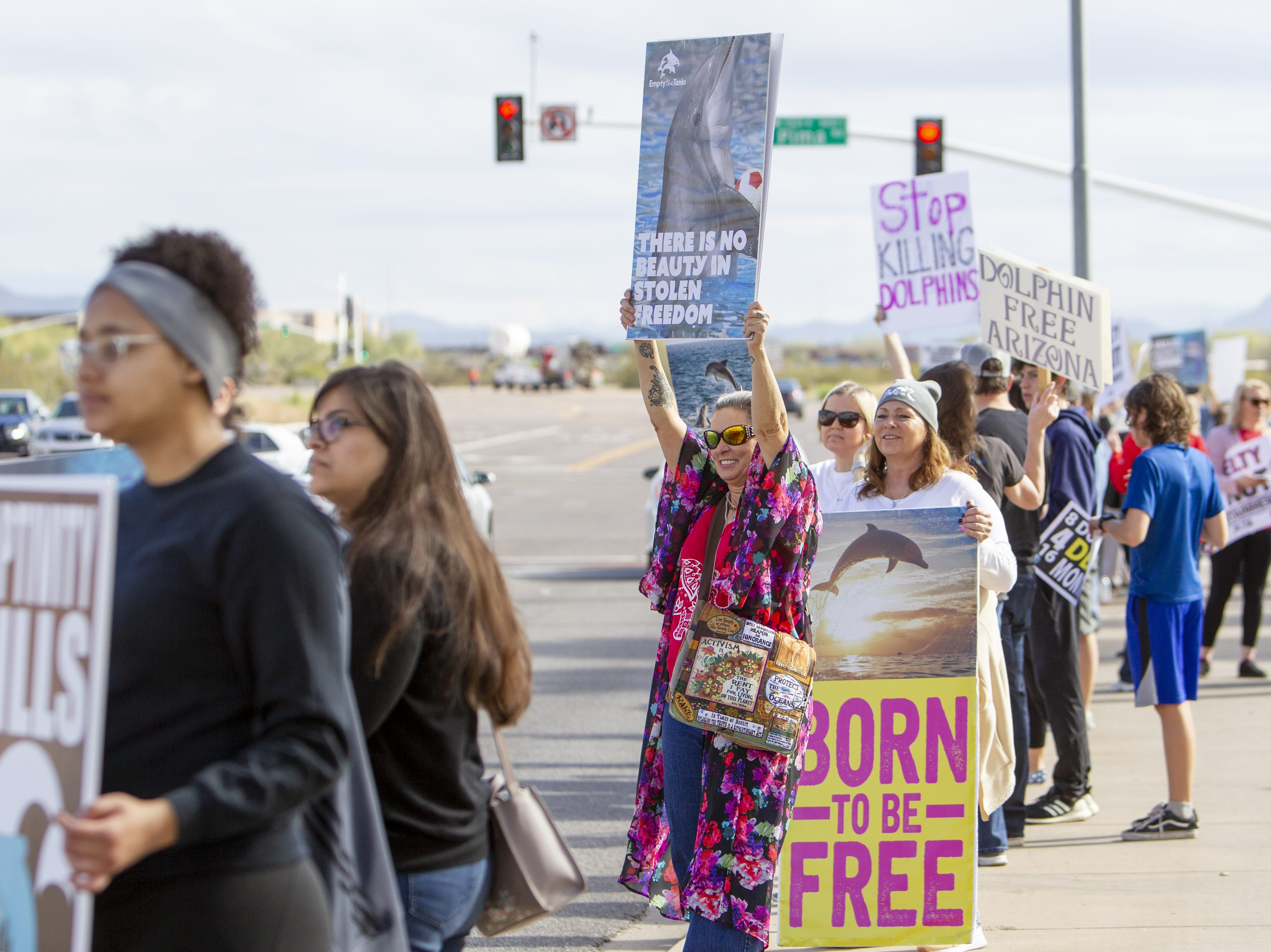 "Debra Toro (center left) and Leslie Acevedo (holding a ""born to be free"" sign) gather along with other Dolphinaris protesters at the intersection of E. Via de Ventura and N. Pima Road in Scottsdale on Feb. 2, 2019. Toro and Acevedo drove down from Las Vegas for the protest, arriving at 2:30 a.m."