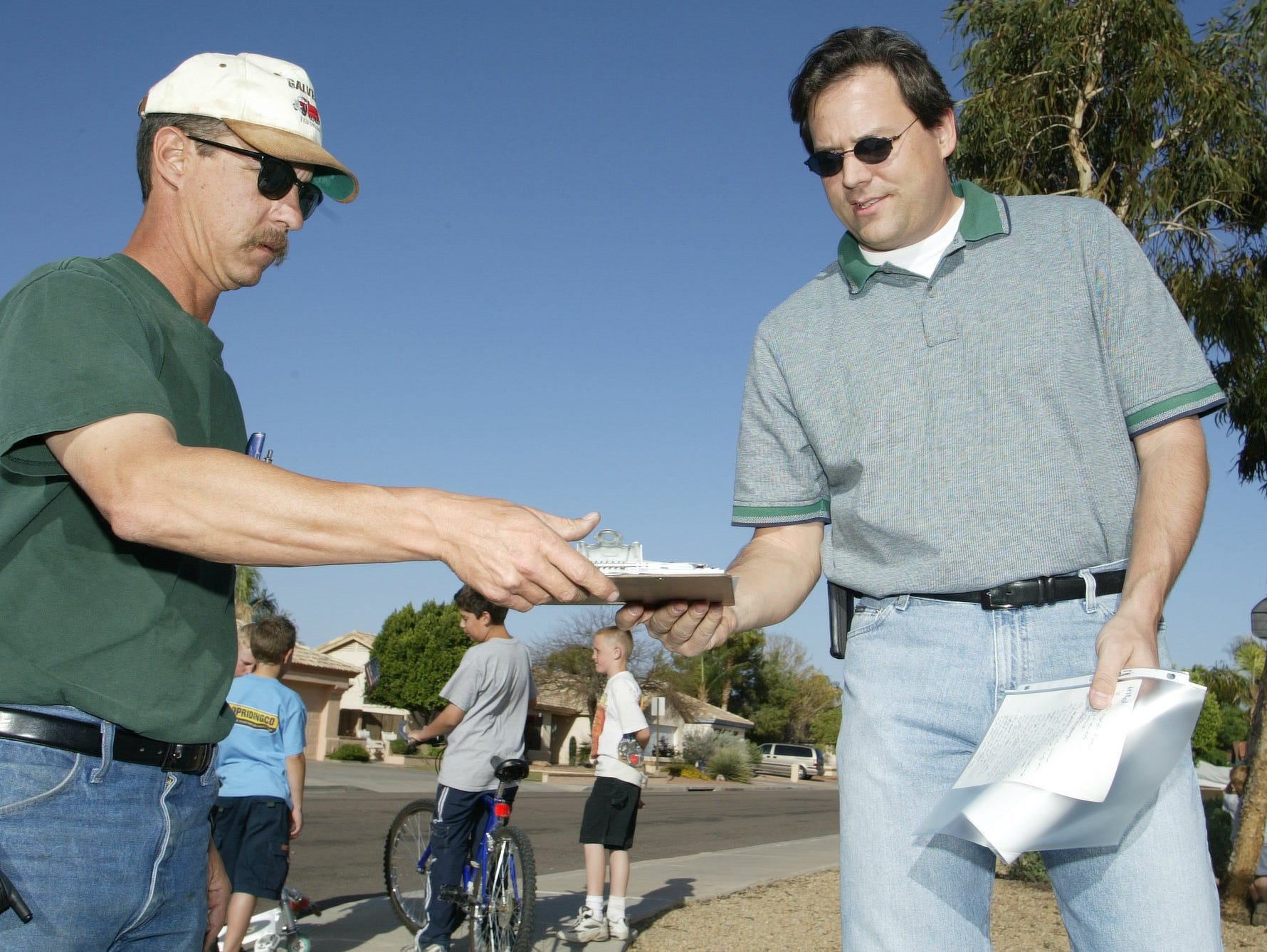 John West, left, hands a signed petition back to Greg Dutton, one of the organizers for a petition regarding go-ped use in Chandler in this 2003 file photo.