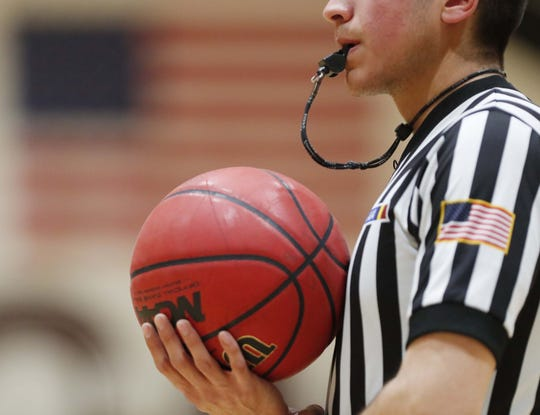 A referee holds a ball during a break between Hamilton and Chandler during the first half in Chandler, Ariz. January 22, 2019.