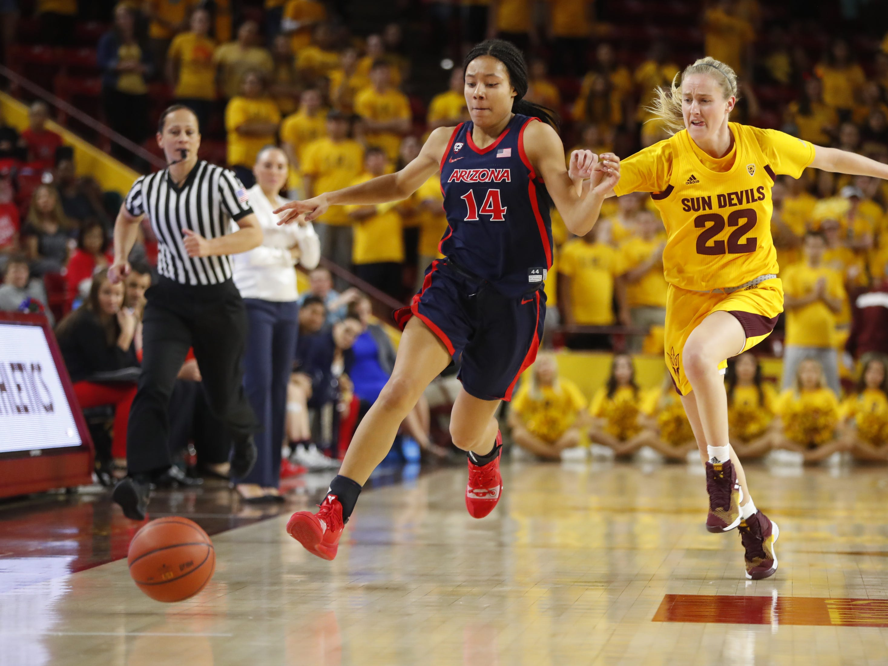 Arizona's Sam Thomas (14) and ASU's Courtney Ekmark (22) chase down a loose ball during the second half at Wells Fargo Arena in Tempe, Ariz. on February 1, 2019.