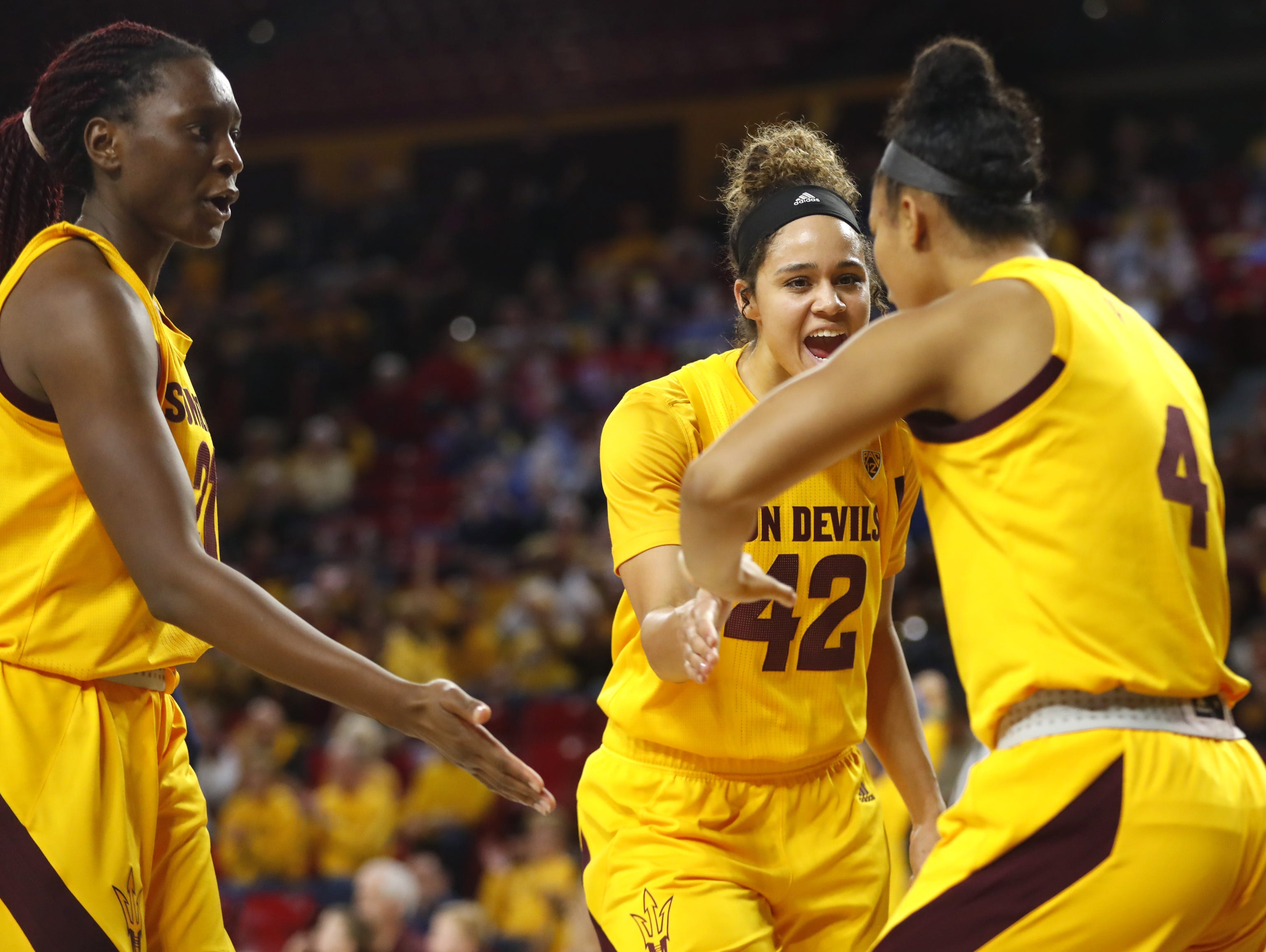 ASU's Sophia Elenga (21) and Kianna Ibis (42) celebrate with Kiara Russell (4) after Russel scored and drew a foul against Arizona during the second half at Wells Fargo Arena in Tempe, Ariz. on February 1, 2019.