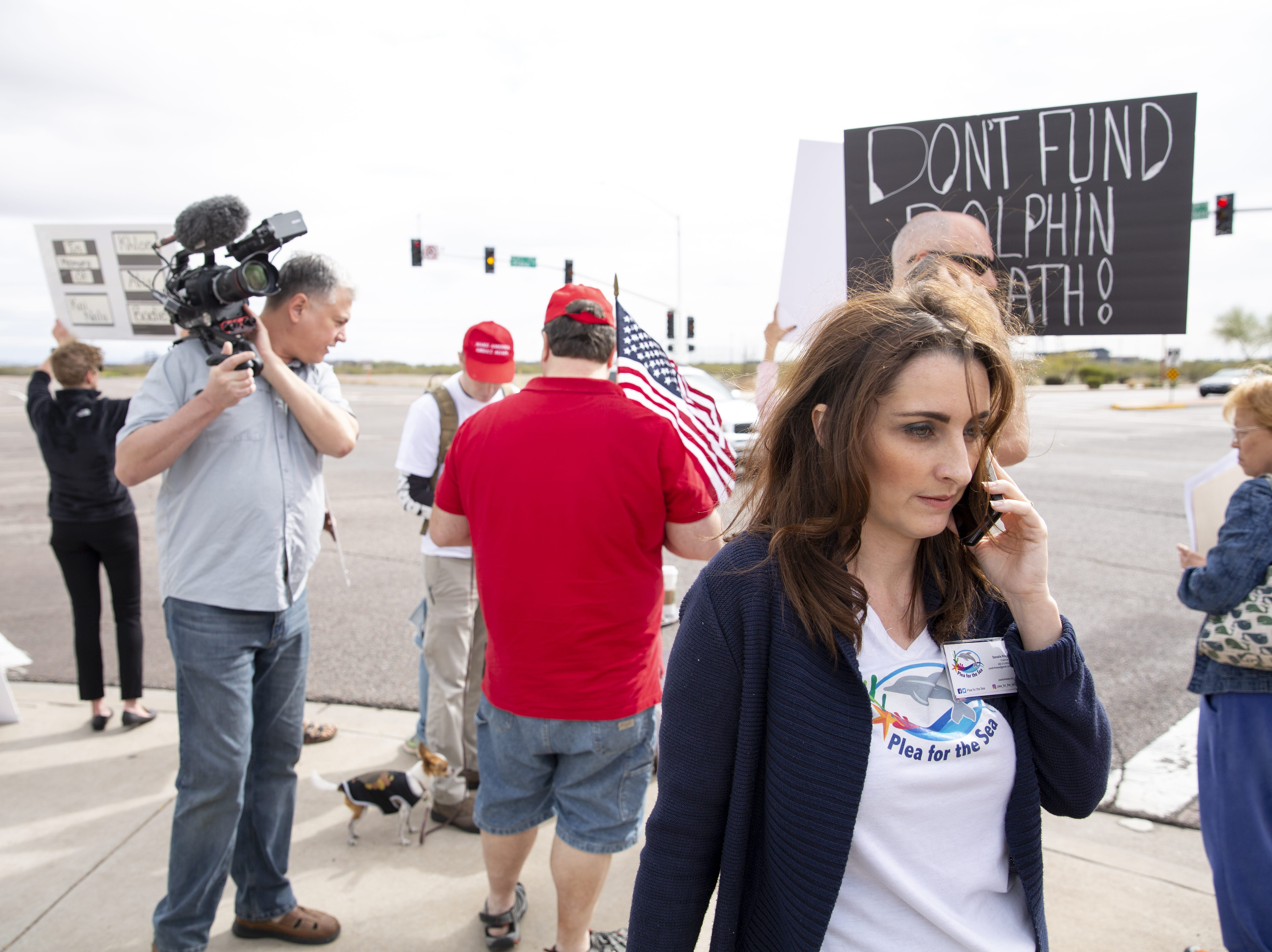 Danielle Riley, the chairman for Plea for the Sea, calls the police after a conflict between Dolphinaris protesters and two counter-protesters on Saturday, Feb. 2, 2019.
