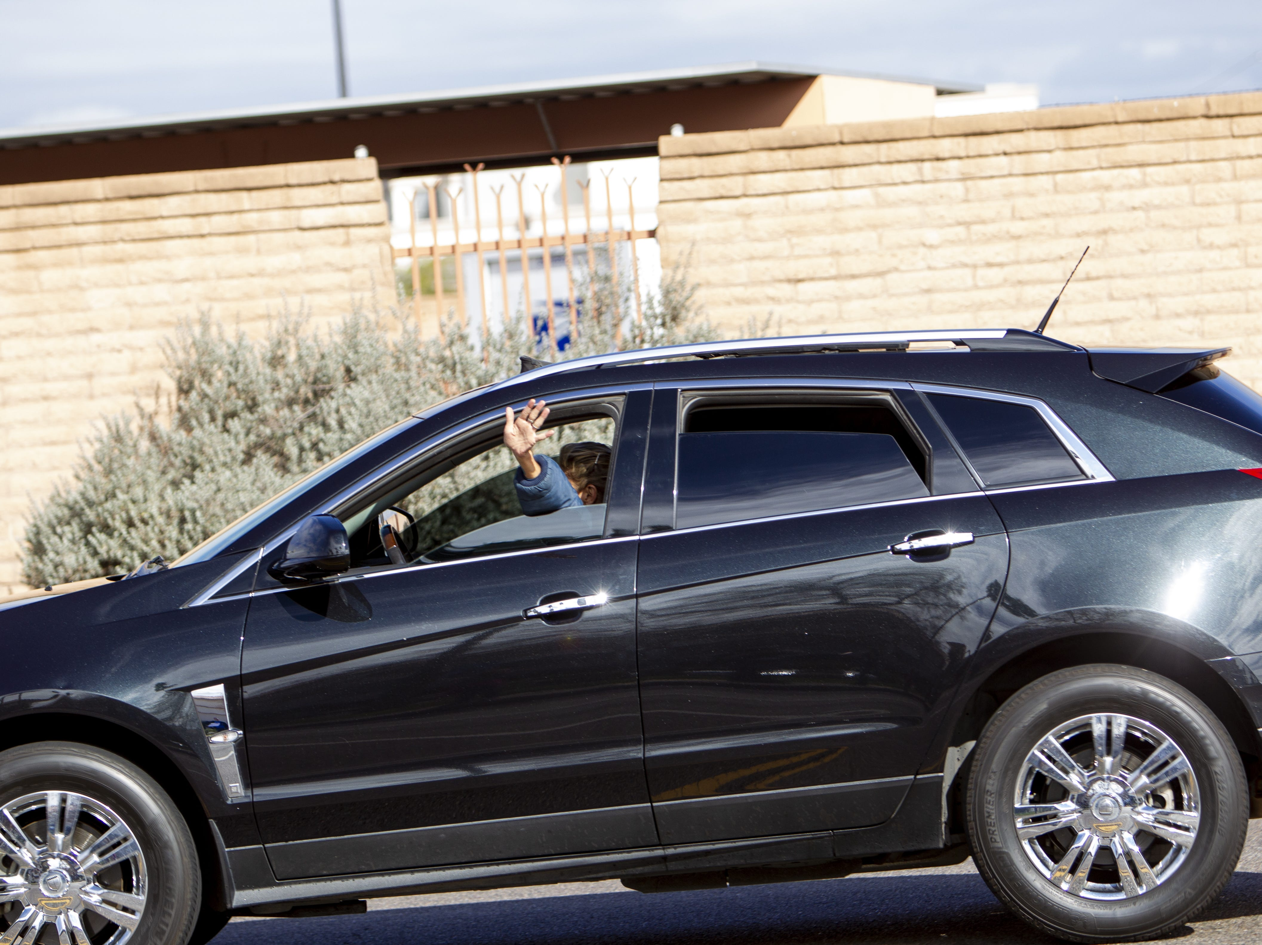 A woman driving by waves to the Dolphinaris protesters at the intersection of E. Via de Ventura and N. Pima Road in Scottsdale on Feb. 2, 2019.
