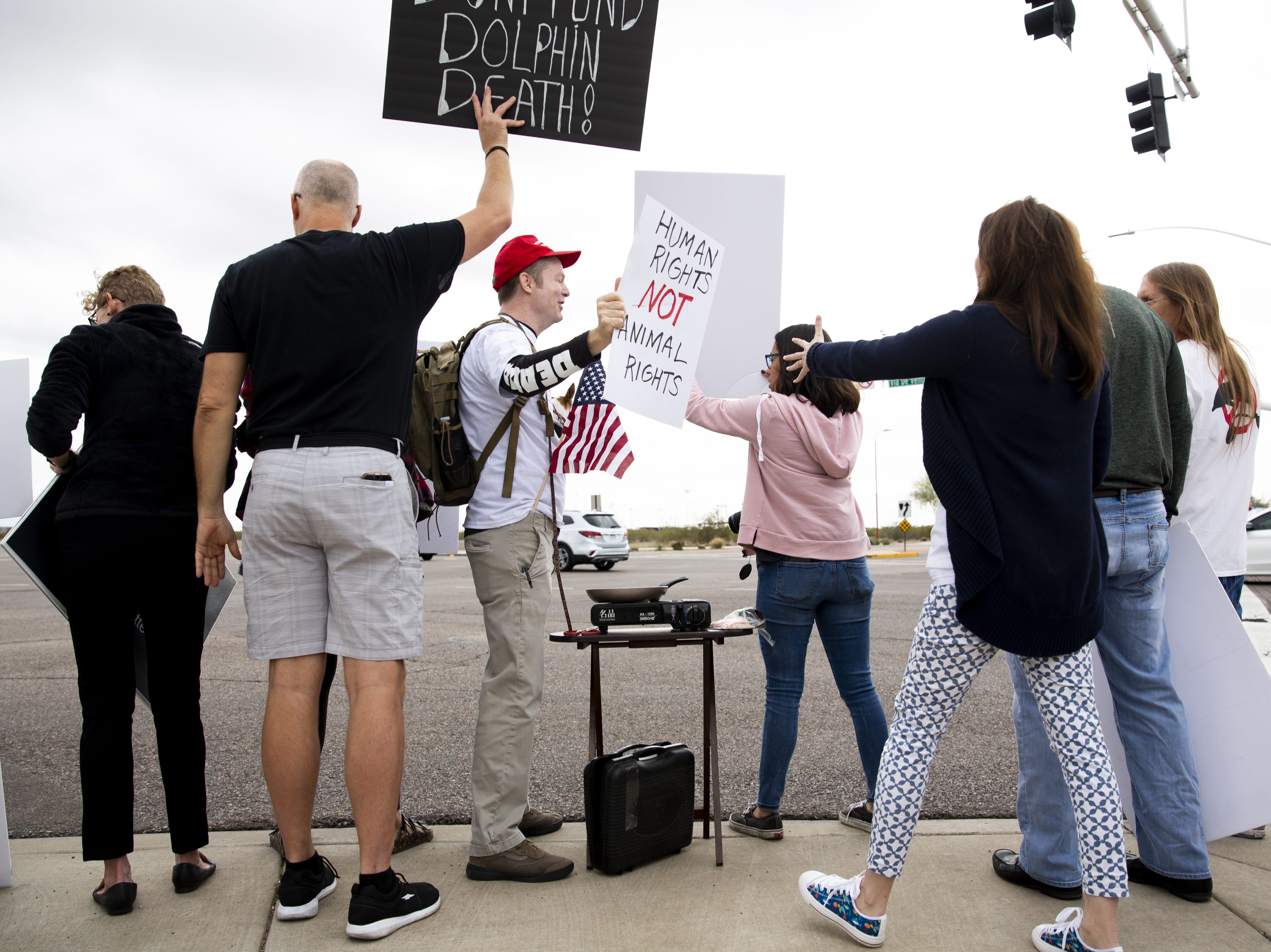 People at the protest against Dolphinaris attempt to block the view of a counter-protester (in red hat) at the intersection of E. Via de Ventura and N. Pima Road. There were two counter-protesters at the event.