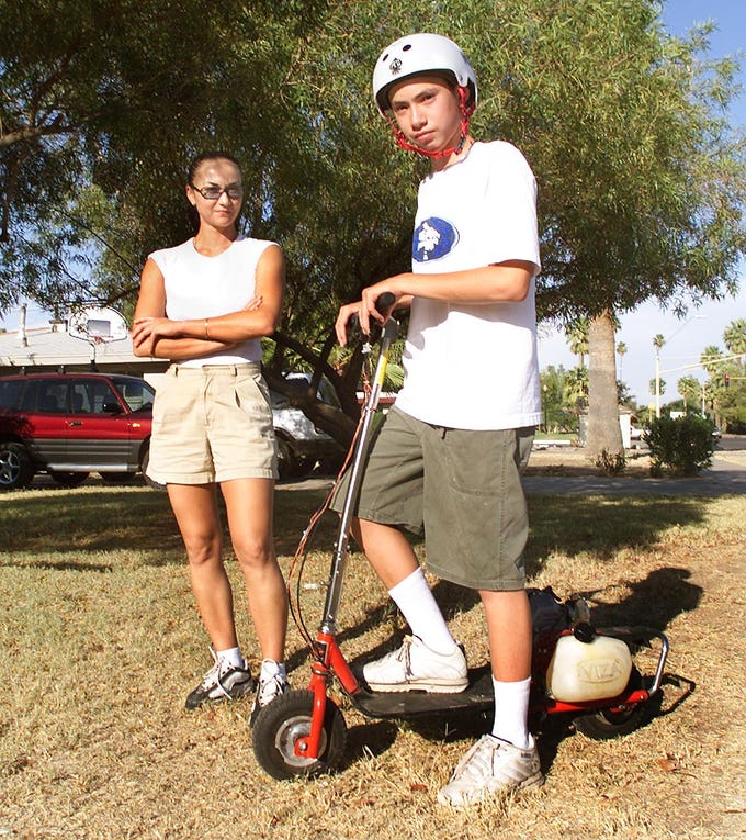 Tai Oliphant shows off his new go-ped, or motorized skateboard, as his mother Su Ling stands behind him in this June 21, 2001 photo from our archives.