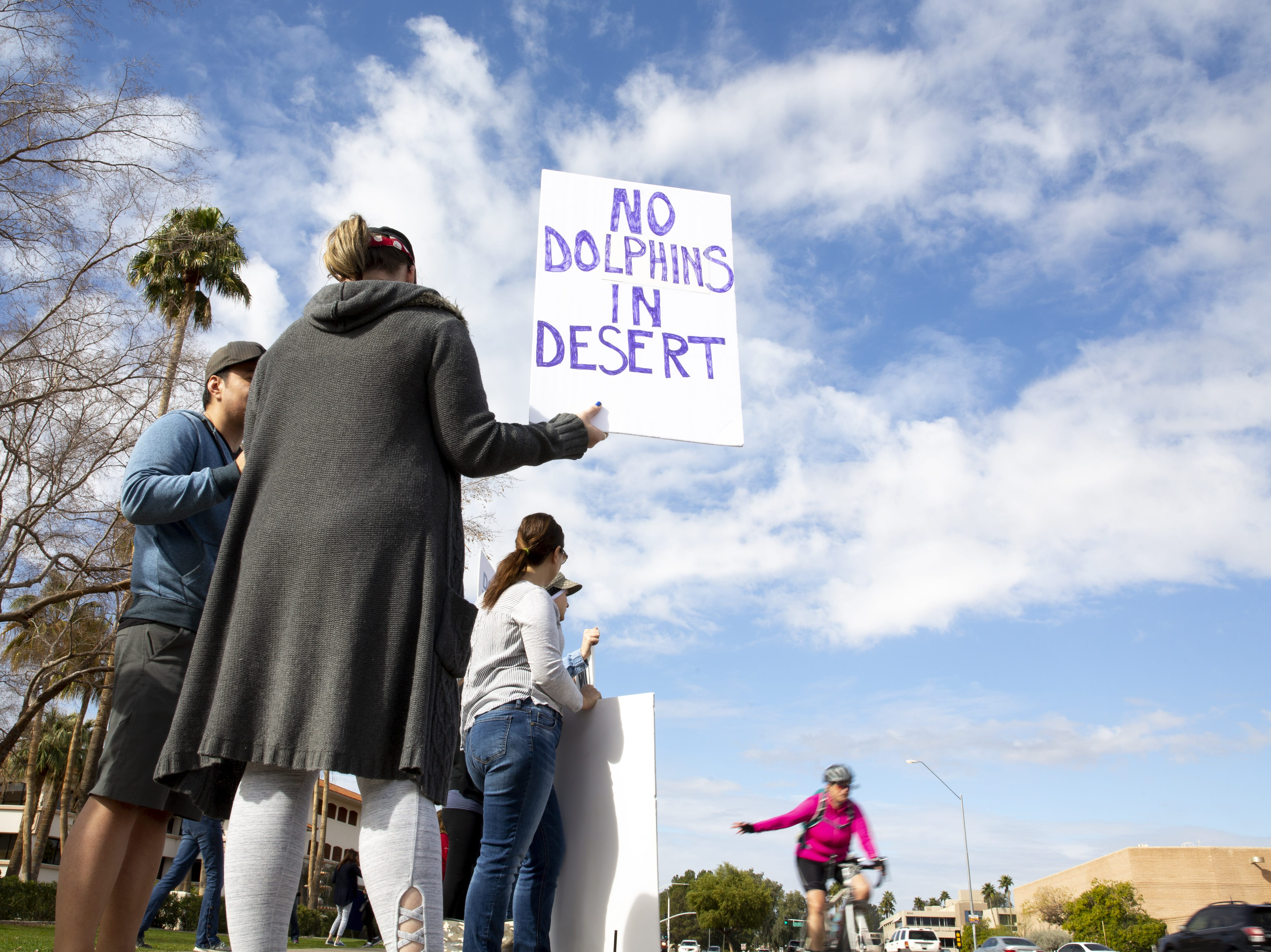 A passing bicyclist waves at people protesting against Dolphinaris at the intersection of E. Via de Ventura and N. Pima Road in Scottsdale on Feb. 2, 2019.