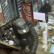 Robbery suspect jumping over store counter.