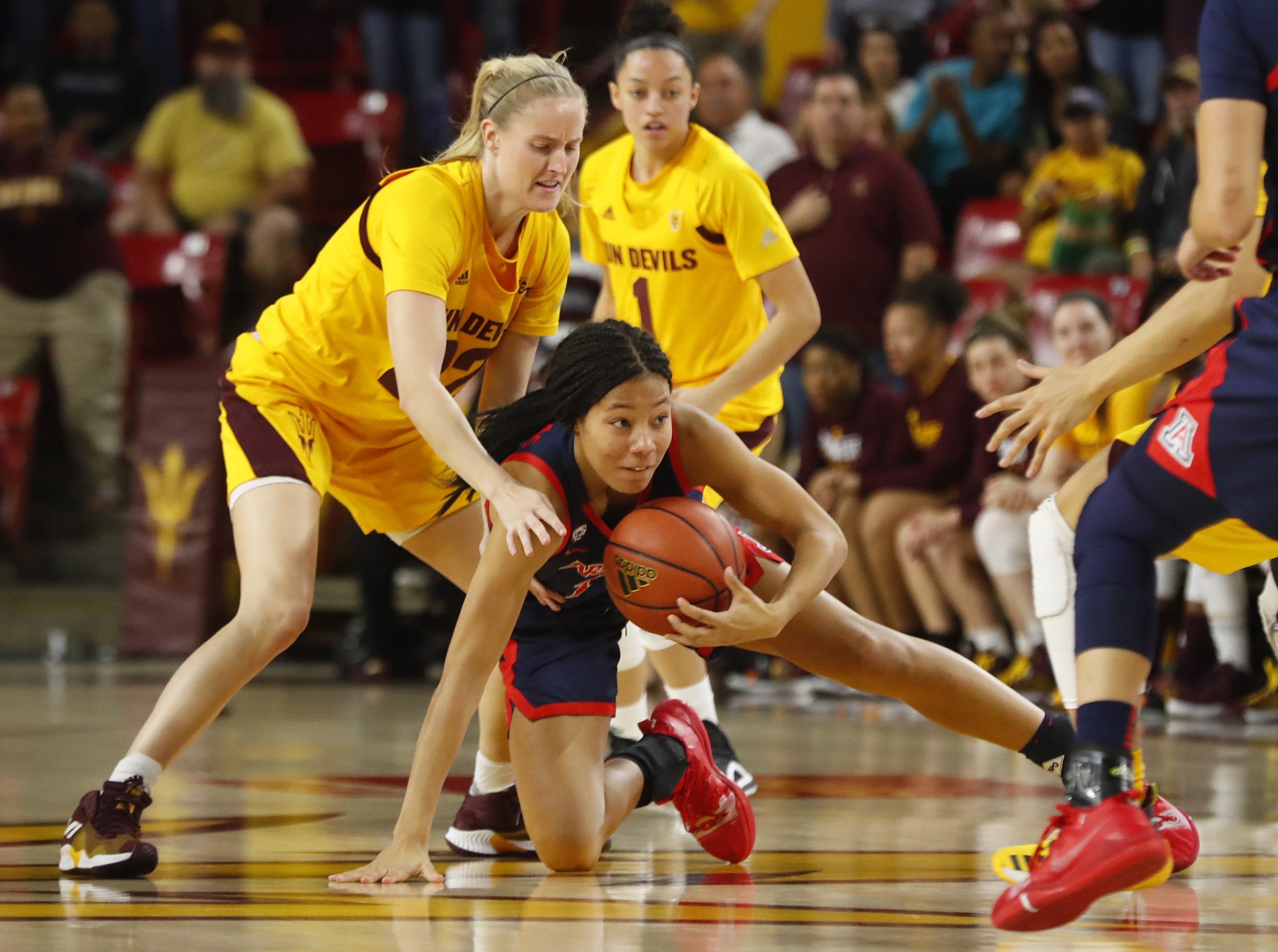 ASU's Courtney Ekmark (22) defends Arizona's Sam Thomas (14) as she recovers a loose ball during the first half at Wells Fargo Arena in Tempe, Ariz. on February 1, 2019.