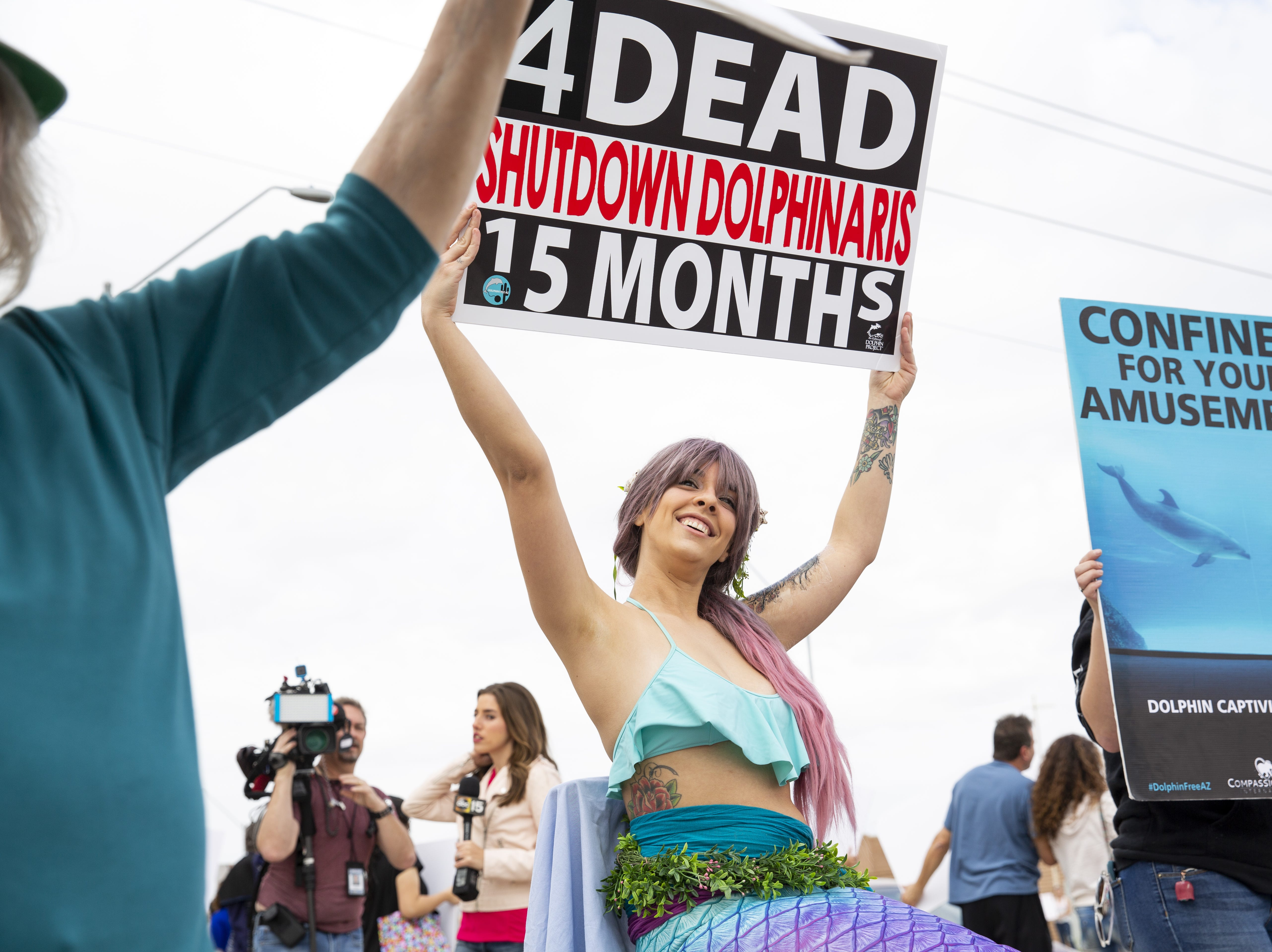 Brami Klin, who goes by @MojaveTheMer on social media, holds a sign in protest of Dolphinaris at the intersection of E. Via de Ventura and N. Pima Road in Scottsdale on Feb. 2, 2019.