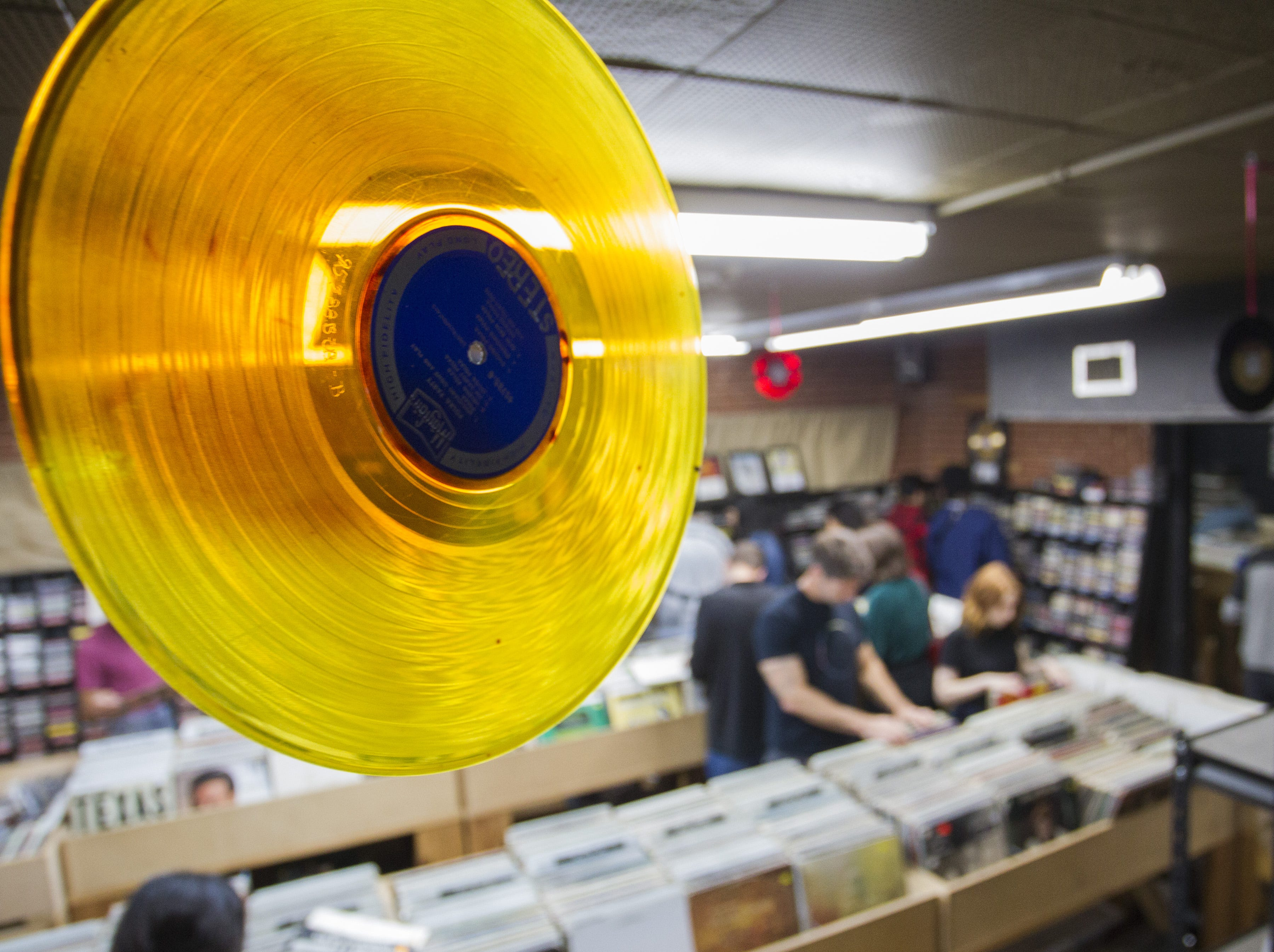 Records hang from the ceiling as music lovers sort through albums at Revolver Records in downtown Phoenix.