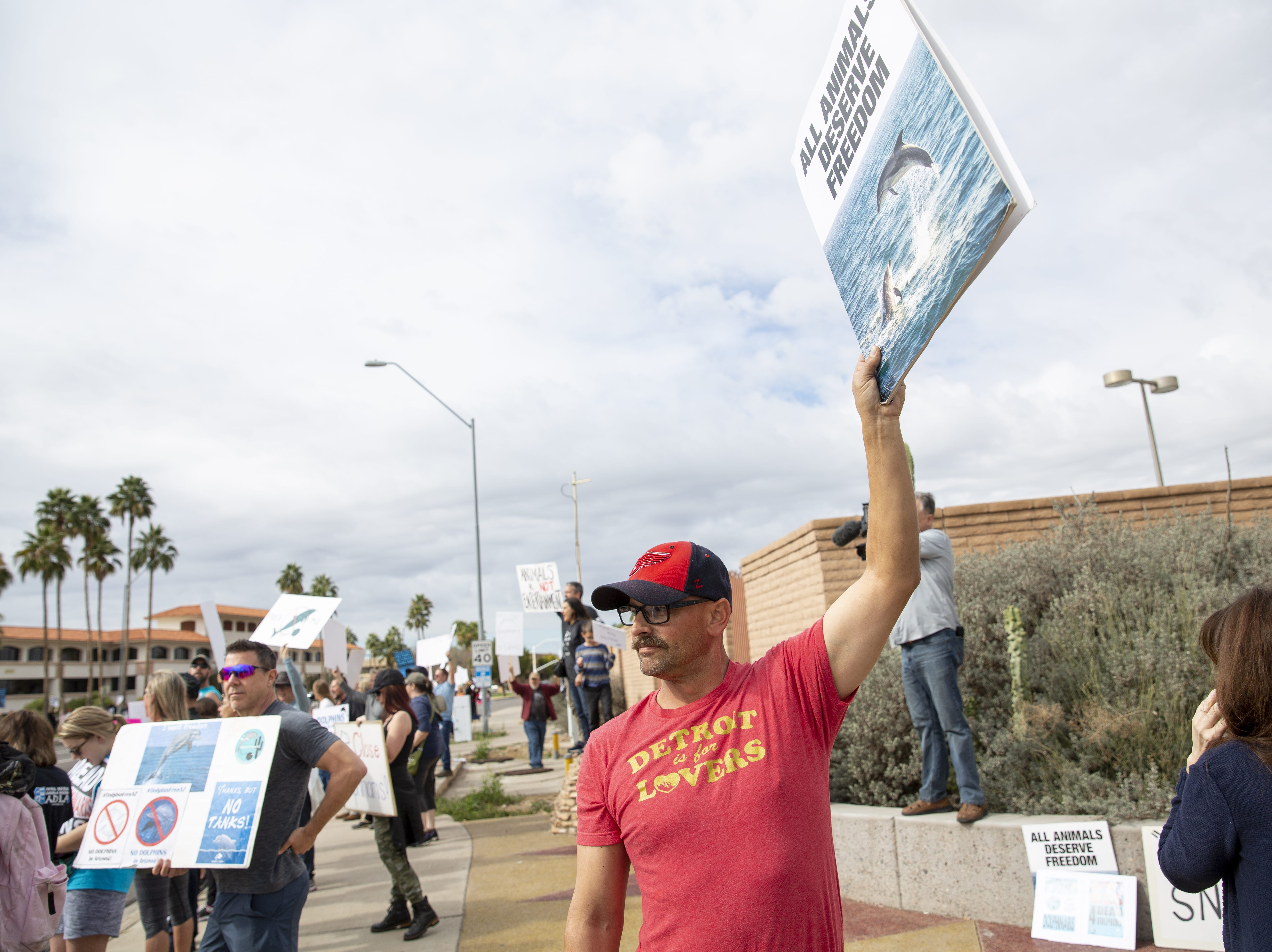 "Dan Peters, of Phoenix, holds a sign that reads ""all animals deserve freedom"" at a protest against Dolphinaris at the intersection of E. Via de Ventura and N. Pima Road in Scottsdale on Feb. 2, 2019."