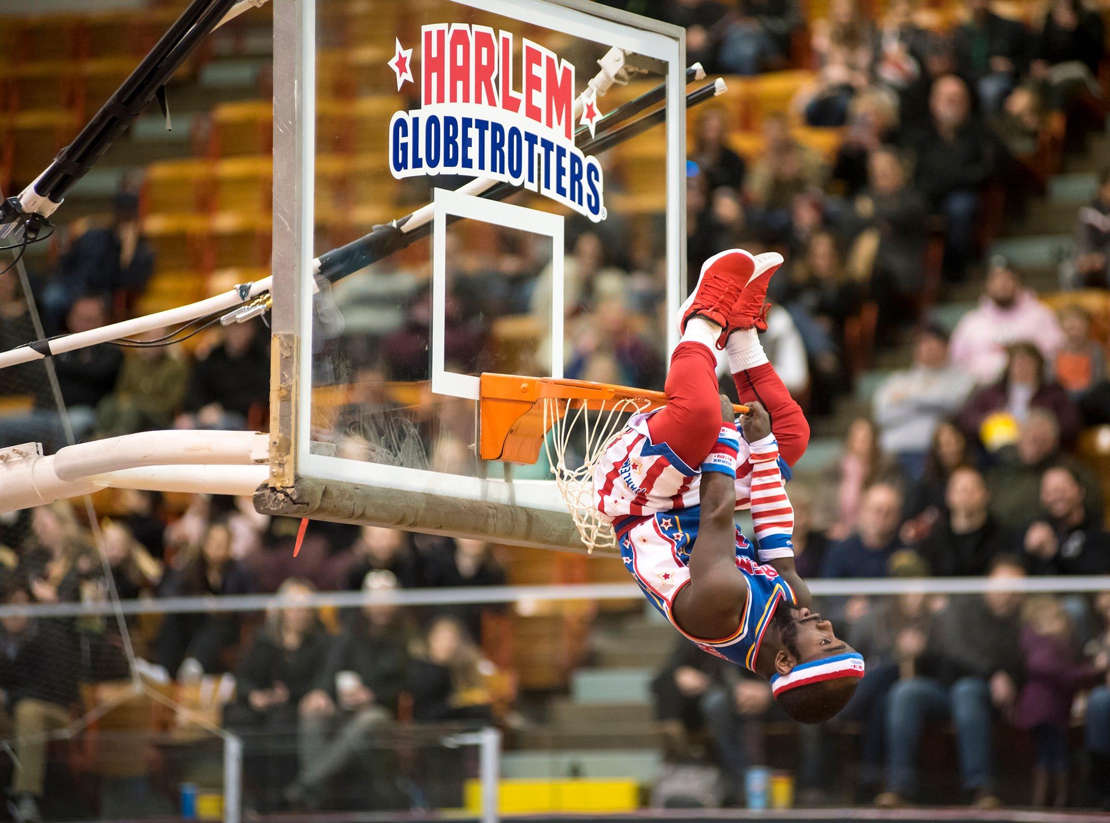 Harlem Globetrotters guard Hot Shot hangs off the hoop  Saturday, Feb. 2, 2019 at McMorran Arena in Port Huron.