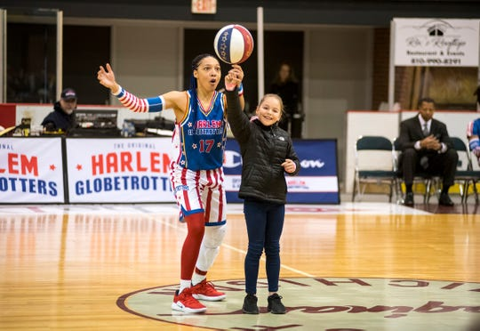 Harlem Globetrotters guard Swish teaches a young fan how to spin a basketball on her finger Saturday, Feb. 2, 2019 at McMorran Arena.