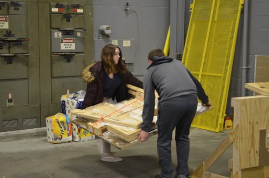 Ella Worley, 14 and Christopher Rochon, 16, carry materials into the Blue Water Area Robotics Alliance's new practice space on Feb. 1, 2018.