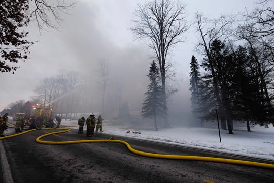 Firefighters work to extinguish a house fire on West Water Street in Kimball Township Saturday afternoon