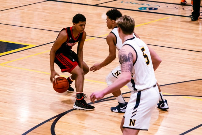 Port Huron High School guard De'Ovion Price attempts to dribble through the Northern defense of Tre Kidd and Braiden McGregor.
