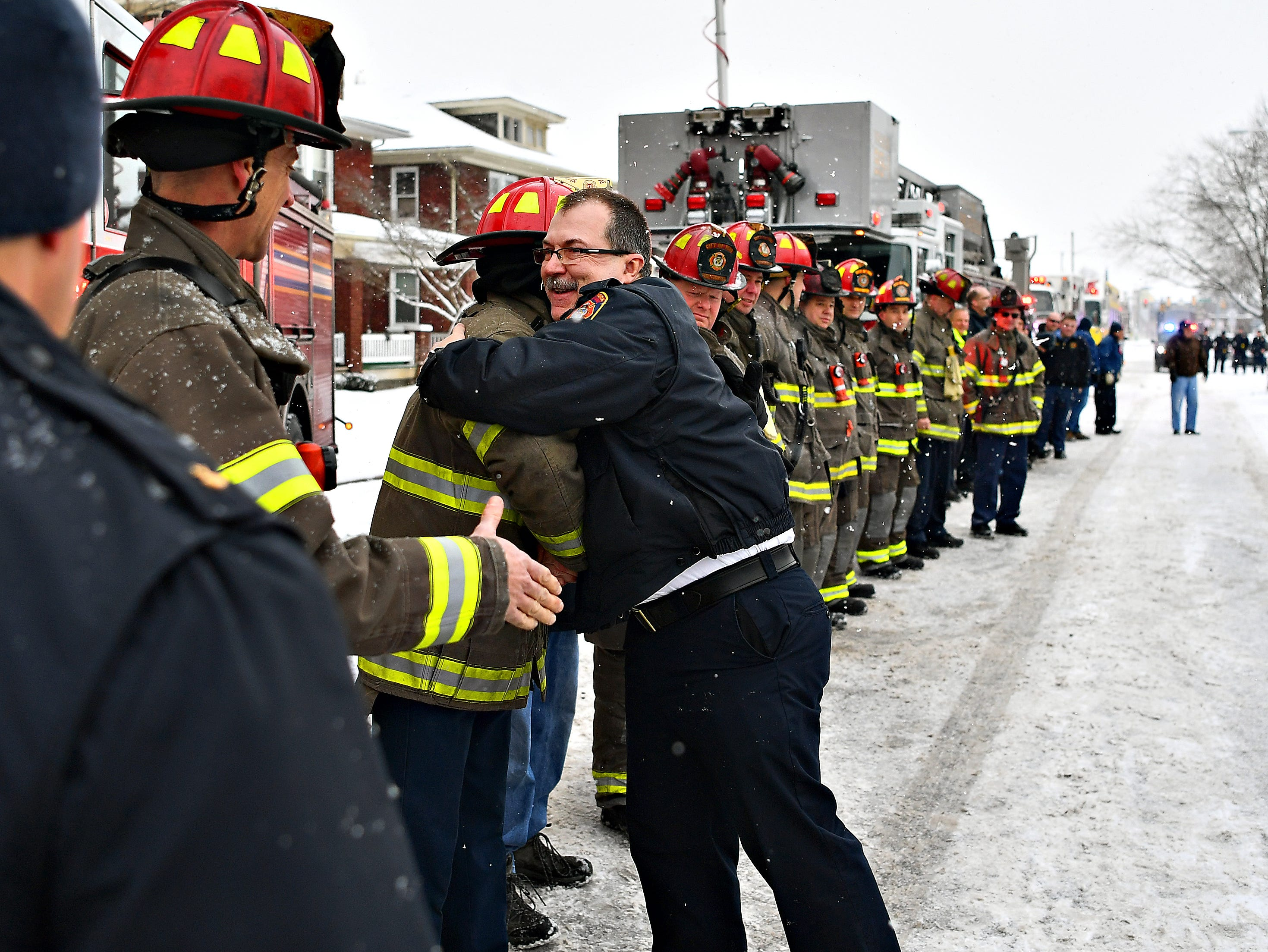 Newly retired York City Fire Chief David Michaels greets area firefighters with a handshake and a hug as family, friends and community members gather to honor him at his home following his final shift in York City, Friday, Feb. 1, 2019. Michaels has been chief since 2012, and has been with York City Department of Fire & Rescue for 28 years. Dawn J. Sagert photo