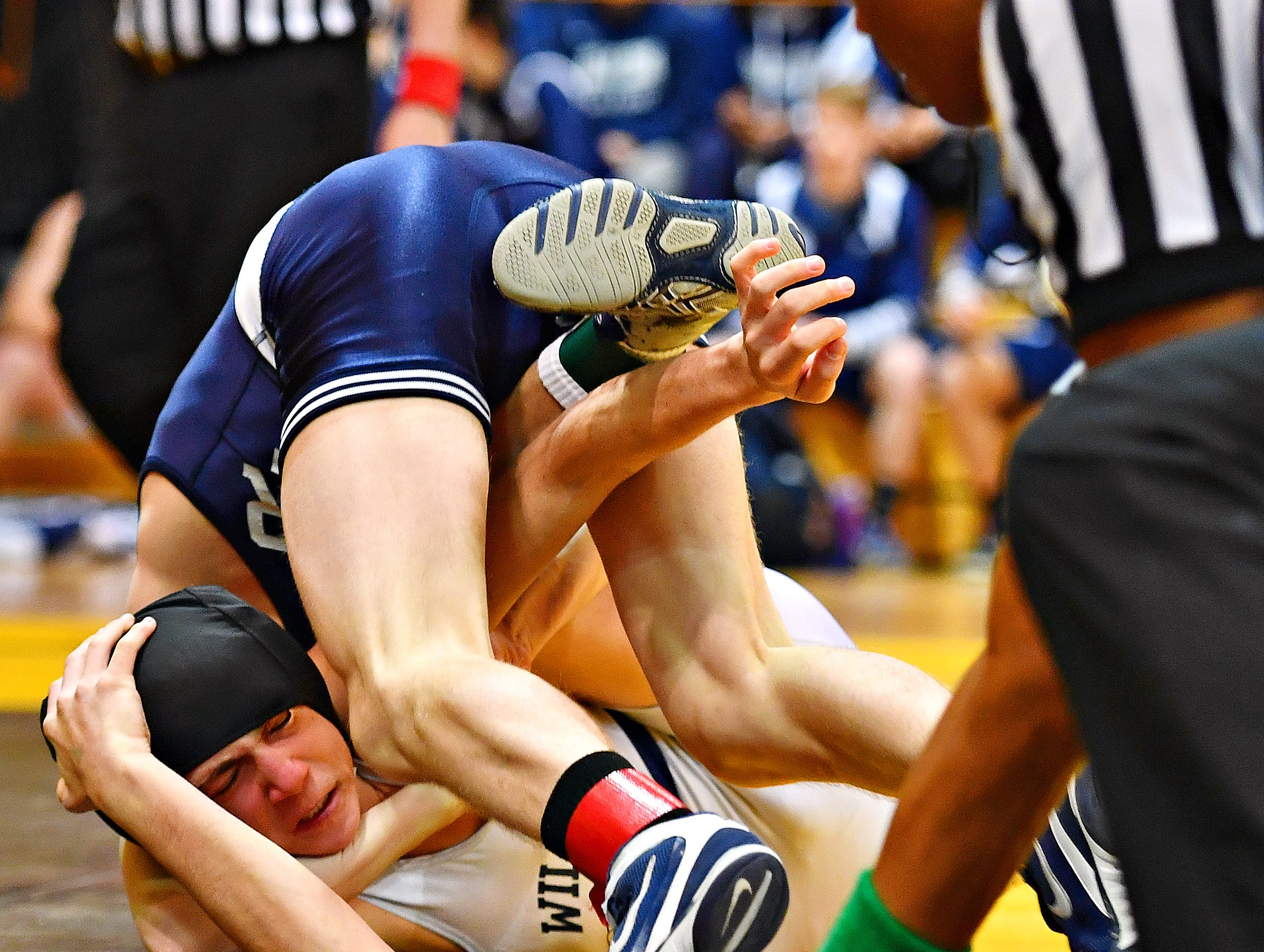Dallastown's Adam Karlie, lower left, wrestles Cedar Cliff's Cole Baer in the 113 pound weight class during District 3, Class 3A wrestling championship action at Milton Hershey High School in Hershey, Saturday, Feb. 2, 2019. Dawn J. Sagert photo