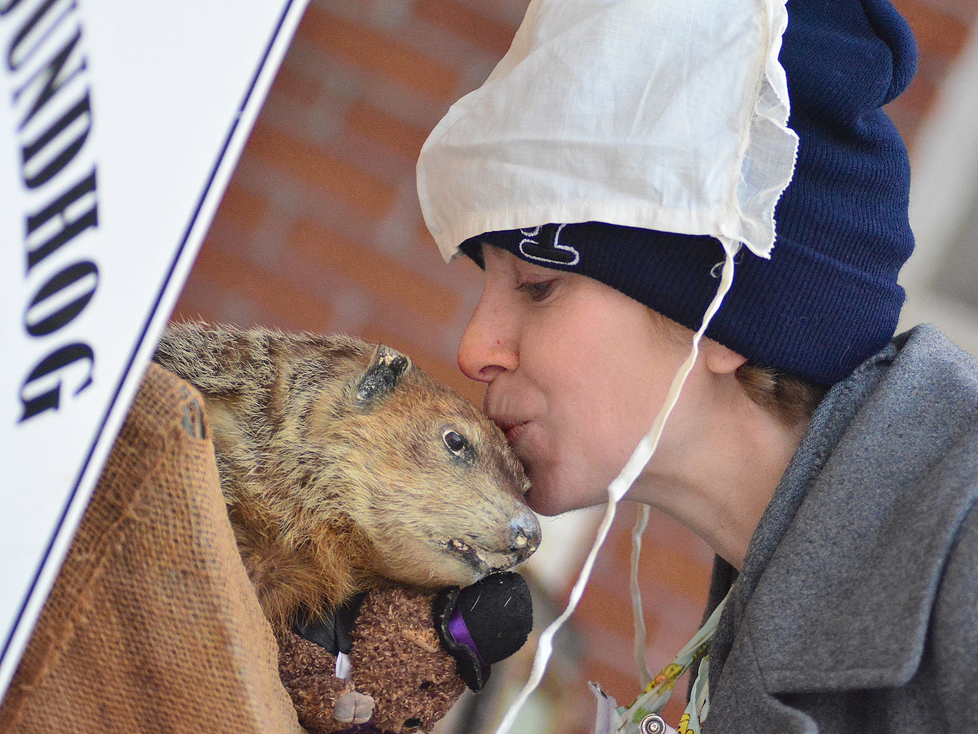 Laura Jensen of York City kisses Poor Richard. New members of the Groundhog lodge wore hats and bibs during the Saturday festivities. Bil Bowden photo.