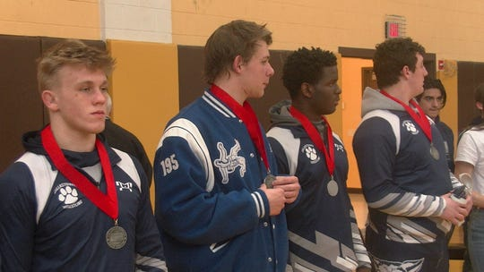 Dallastown wrestlers accept silver medals following a loss to Cedar Cliff in the District 3 Class 3A title match Saturday.