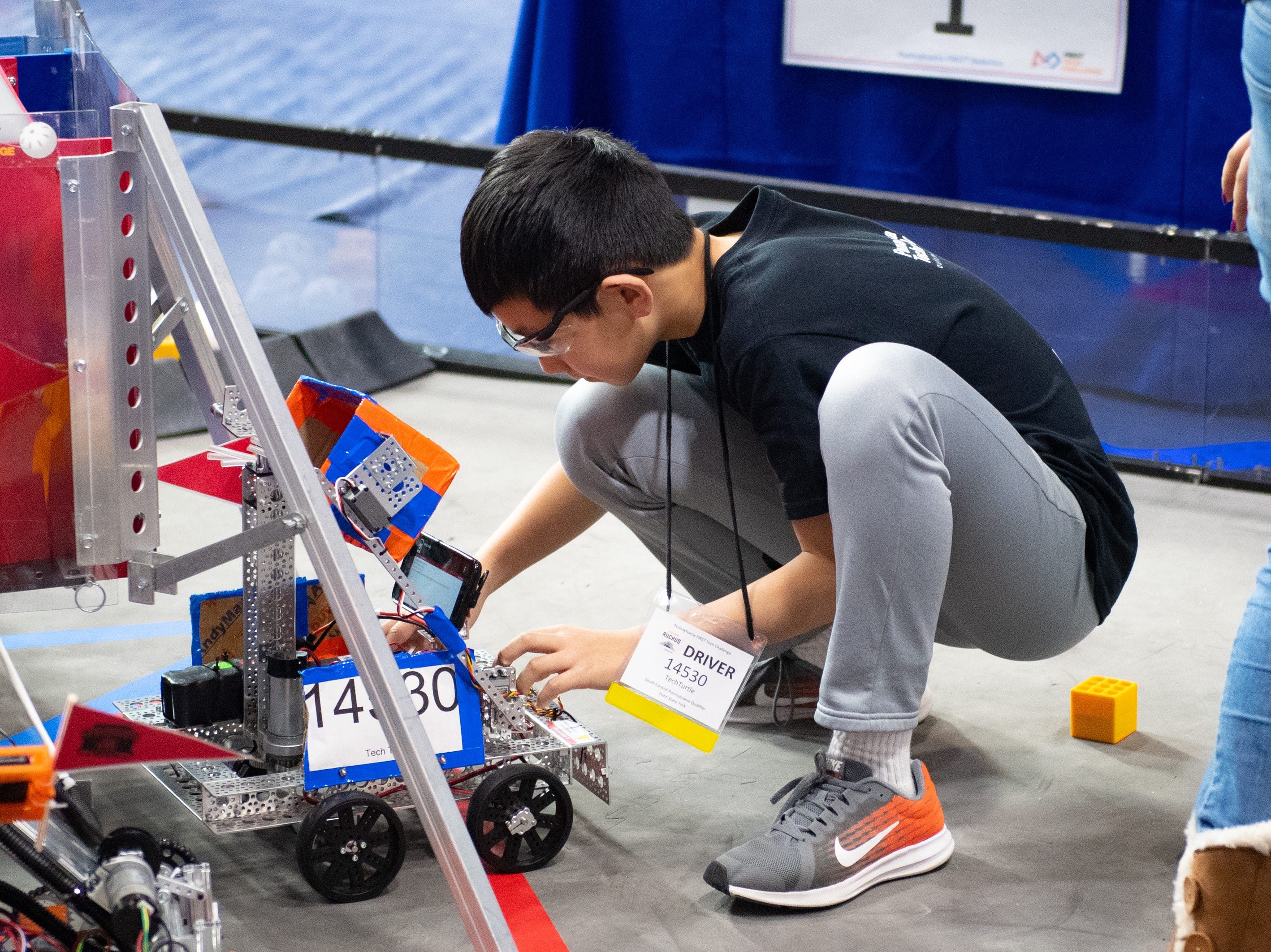 Before the each match starts, players secure their robots to the spaceship in their specific starting positions during the First Tech Challenge robotics competition at Penn State York, February 2, 2019.
