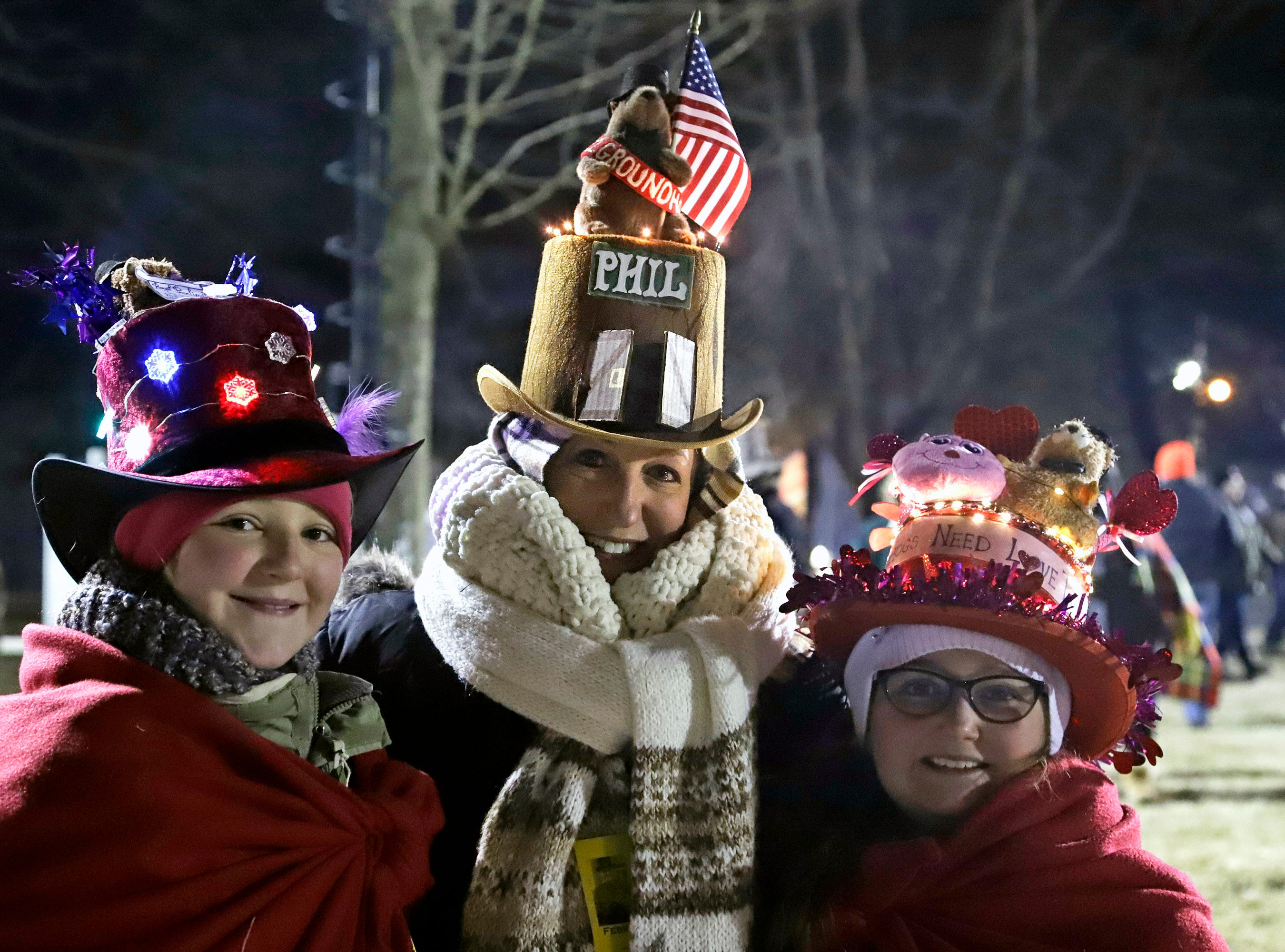 Lisa Gibson, center, and her daughters Josie, left, and AneGiguere of Pittsburgh, arrive early to celebrate the 133rd Groundhog Day on Gobbler's Knob in Punxsutawney, Pa. Saturday, Feb. 2, 2019. It is the second Groundhog Day trek to Gobbler's Knob for the family. (AP Photo/Gene J. Puskar)