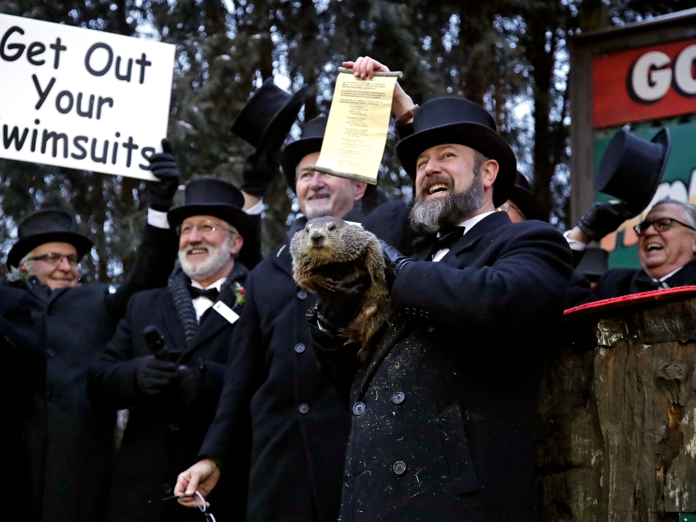 Groundhog Club co-handler Al Dereume, second from right, holds Punxsutawney Phil, the weather prognosticating groundhog, during the 133rd celebration of Groundhog Day on Gobbler's Knob in Punxsutawney, Pa. Saturday, Feb. 2, 2019. Phil's handlers said that the groundhog has forecast an early spring.