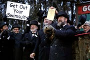 Groundhog Club co-handler Al Dereume, second from right, holds Punxsutawney Phil on Feb. 2.