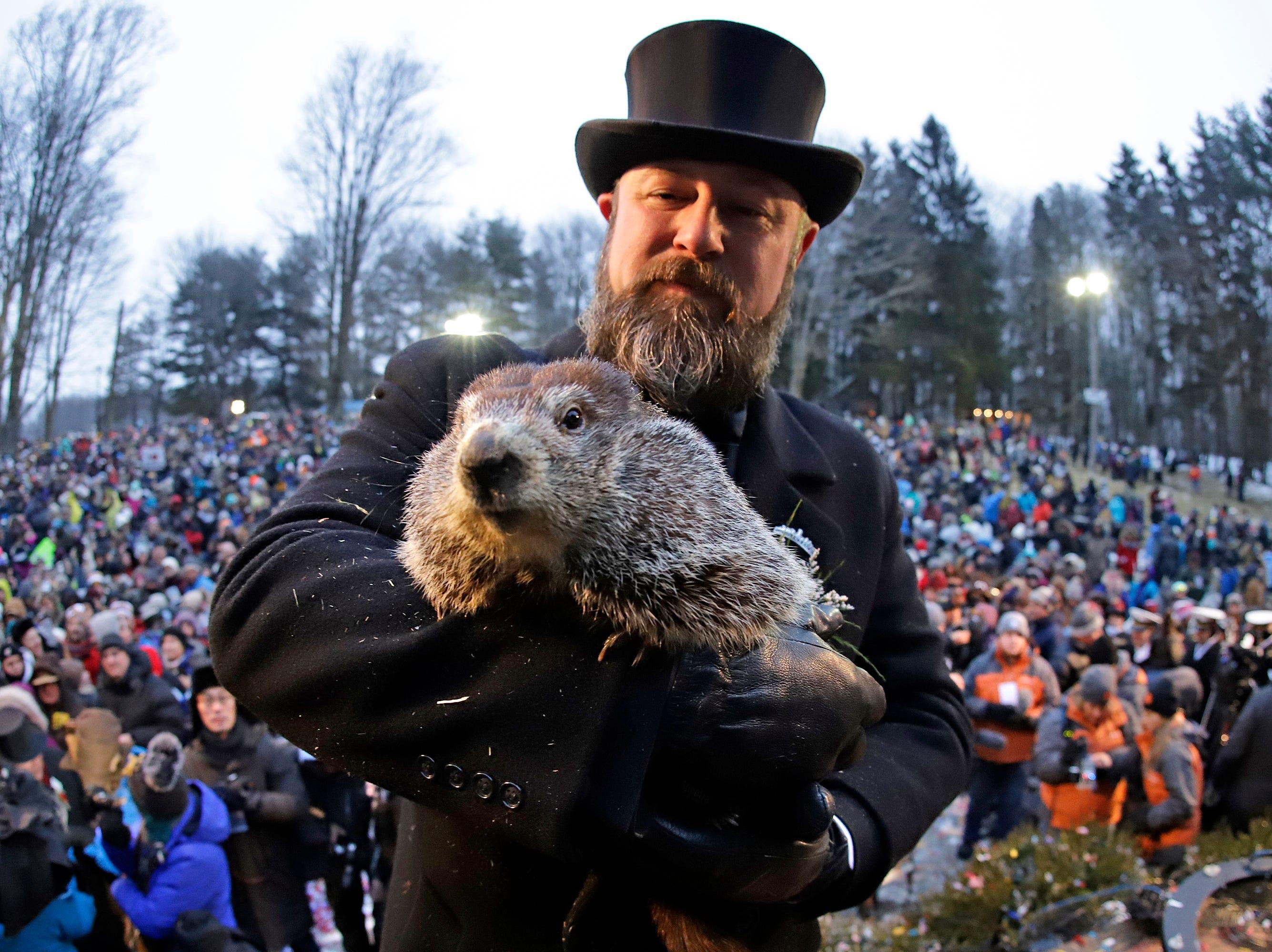 Groundhog Club co-handler Al Dereume, right, holds Punxsutawney Phil, the weather prognosticating groundhog, during the 133rd celebration of Groundhog Day on Gobbler's Knob in Punxsutawney, Pa. Saturday, Feb. 2, 2019. Phil's handlers said that the groundhog has forecast an early spring. (AP Photo/Gene J. Puskar)