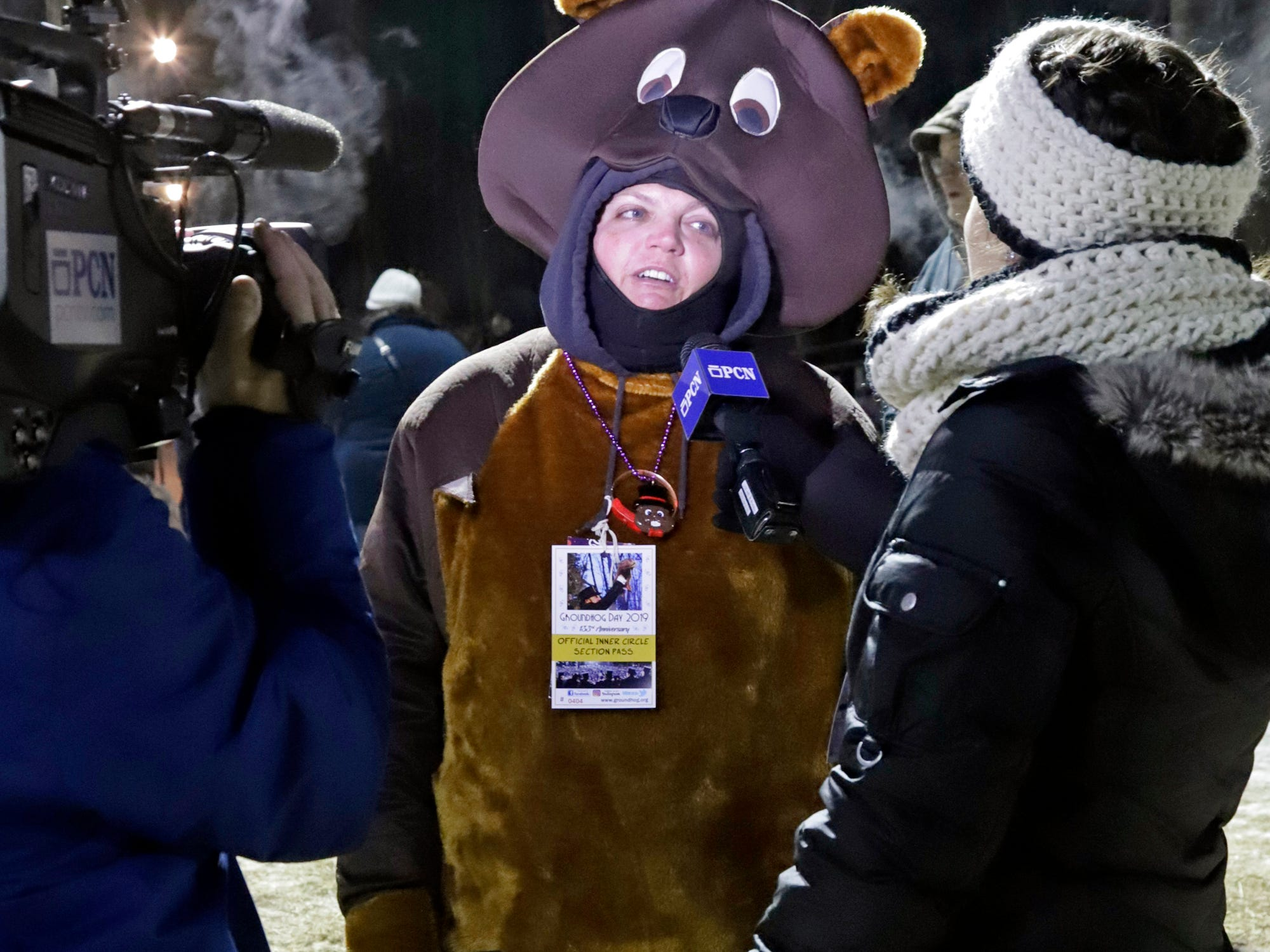 Katie Wolf of New Cumberland, Pa., center, wearing a groundhog costume is interviewed as she arrives for the 133rd Groundhog Day celebration on Gobbler's Knob in Punxsutawney, Pa. Saturday, Feb. 2, 2019. (AP Photo/Gene J. Puskar)