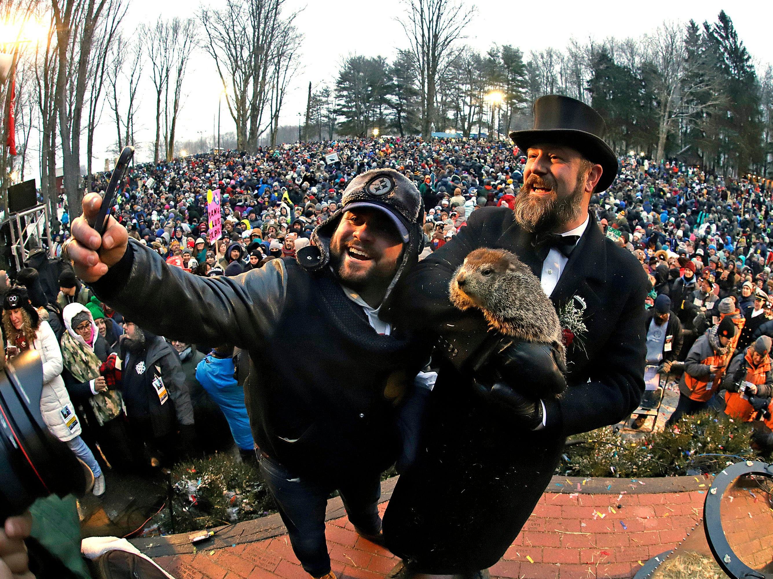 Groundhog Club co-handler Al Dereume, right, holds Punxsutawney Phil, the weather prognosticating groundhog, and poses for a selfie with a groundhog fan, in front of the crowd gathered for the 133rd celebration of Groundhog Day on Gobbler's Knob in Punxsutawney, Pa. Saturday, Feb. 2, 2019. Phil's handlers said that the groundhog has forecast an early spring. (AP Photo/Gene J. Puskar)