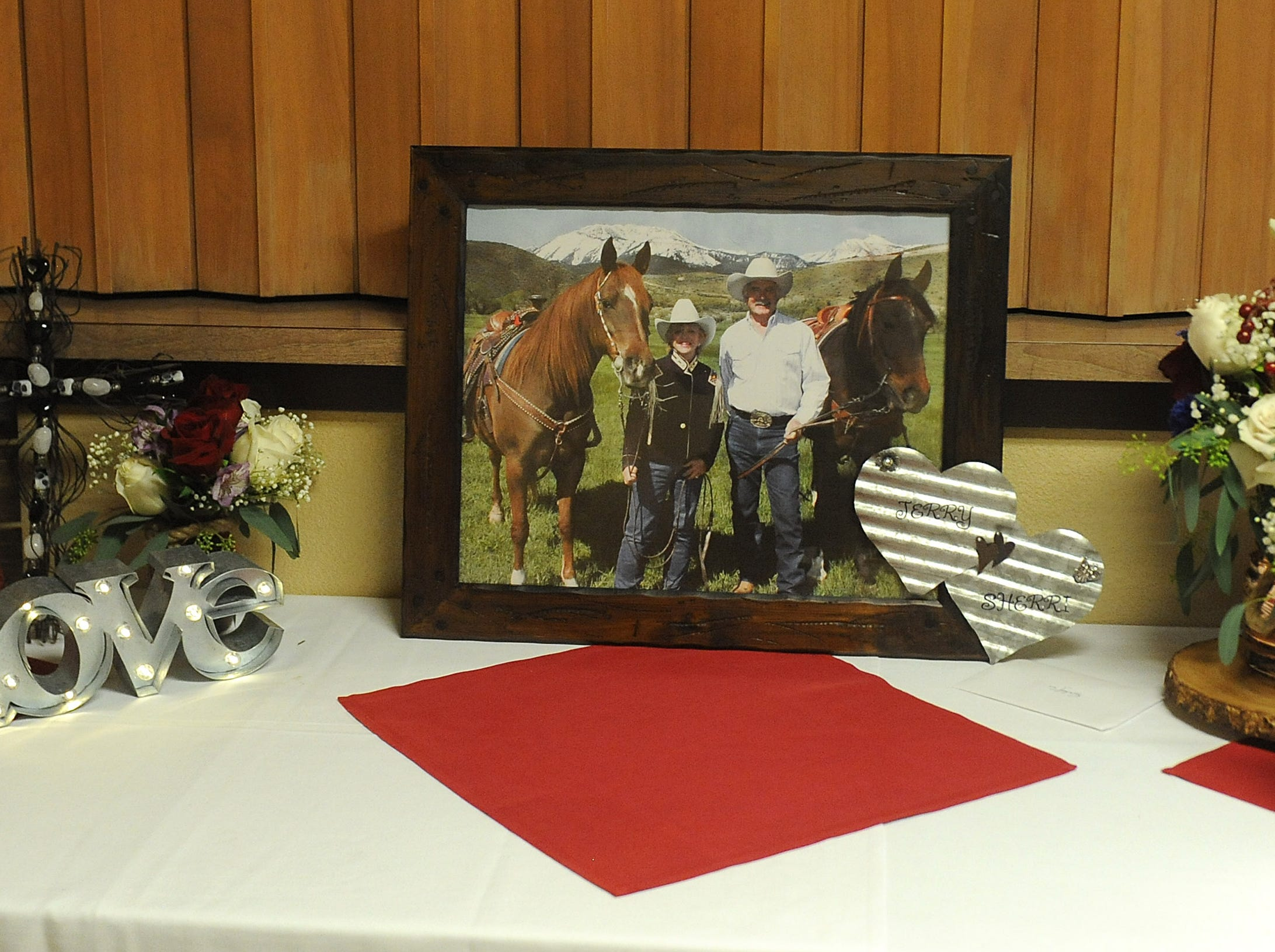 A collection of photos is seen as friends and family gather to pay their respects during a memorial service for Jerry and Sherri David at the Reno Elks Lodge on Feb. 1, 2019.