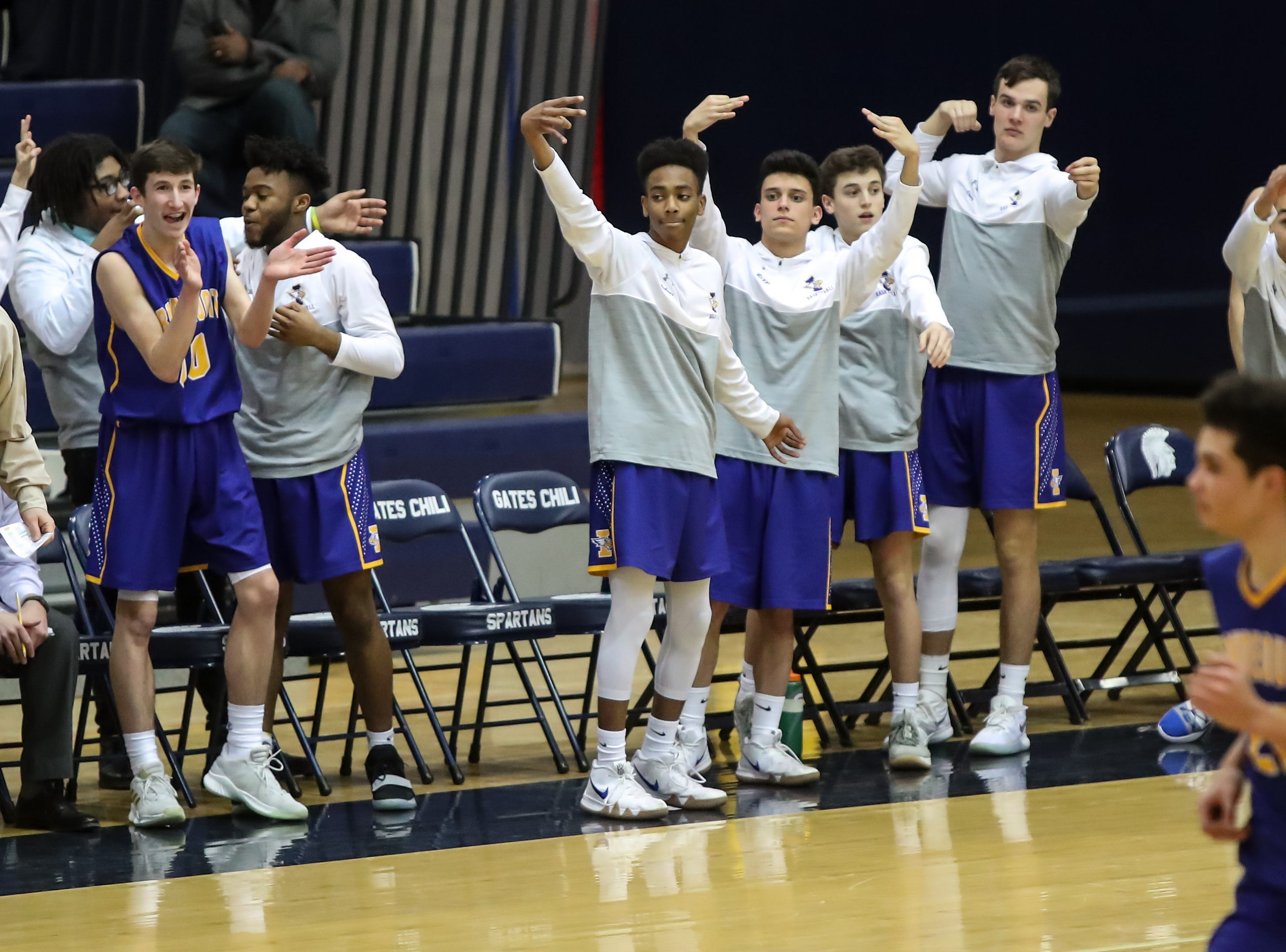 The Irondequoit Eagles bench celebrates a 3-pointer against the Gates Chili Spartans during a Section V high school boys basketball game at Gates Chili High School on Feb. 1, 2019.
