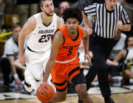 Oregon State guard Ethan Thompson, front, picks up the ball as Colorado forward Lucas Siewert follows in the first half of an NCAA college basketball game Thursday, Jan. 31, 2019, in Boulder, Colo.