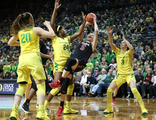 Utah's Megan Huff, enter, shots as she falls under pressure from Oregon's Sabrina Ionescu, left, Ruthy Hebard and Taylor Chavez, right, during the third quarter of an NCAA college basketball game Friday, Feb. 1, 2019, in Eugene, Ore.
