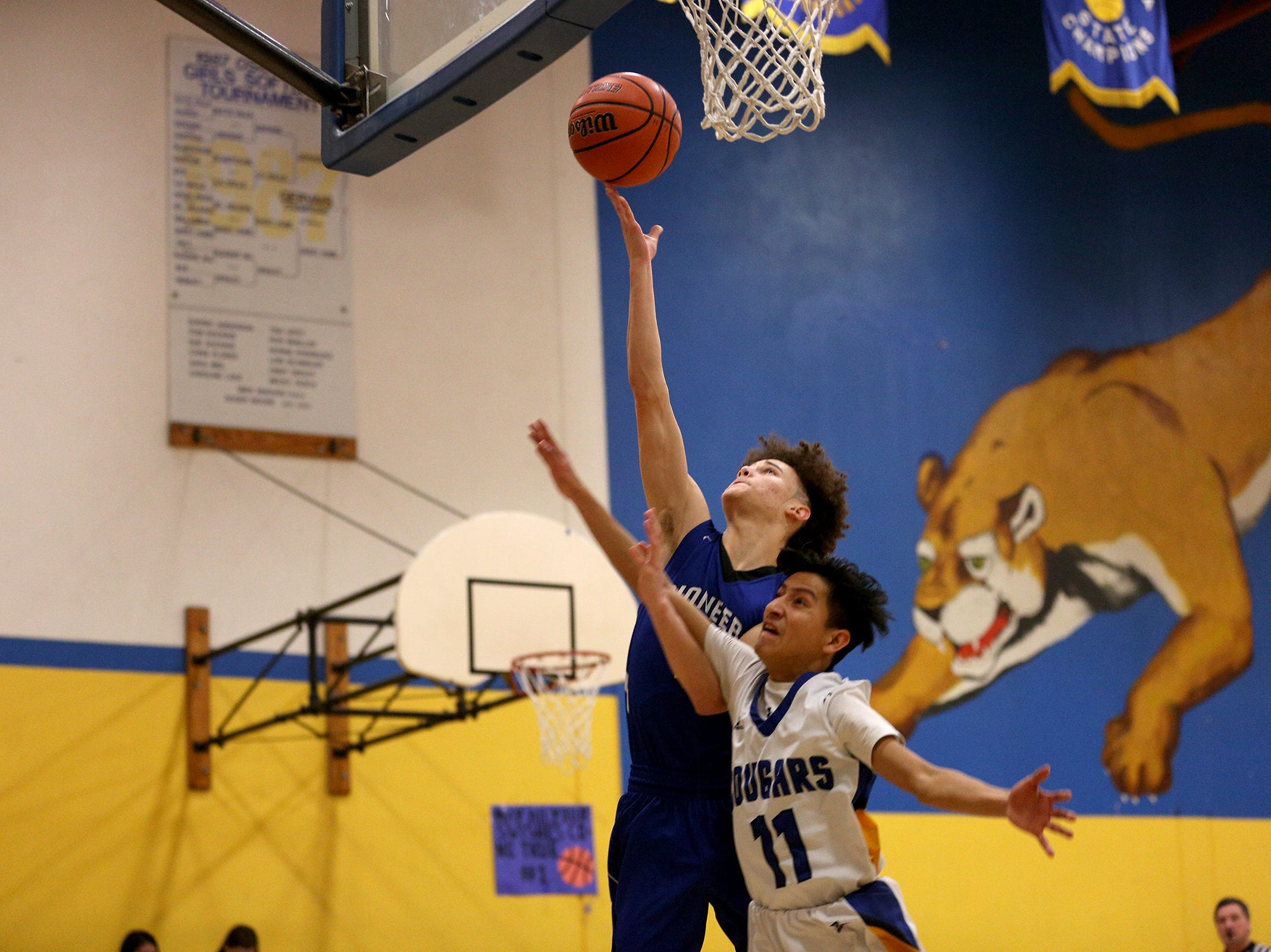 Western Christian's Johnny Williams (11) attempts a layup as Gervais' Armando Tarula (11) tries to defend him during the Gervais High School boys basketball game against Western Christian in Gervais on Friday, Feb. 1, 2019.